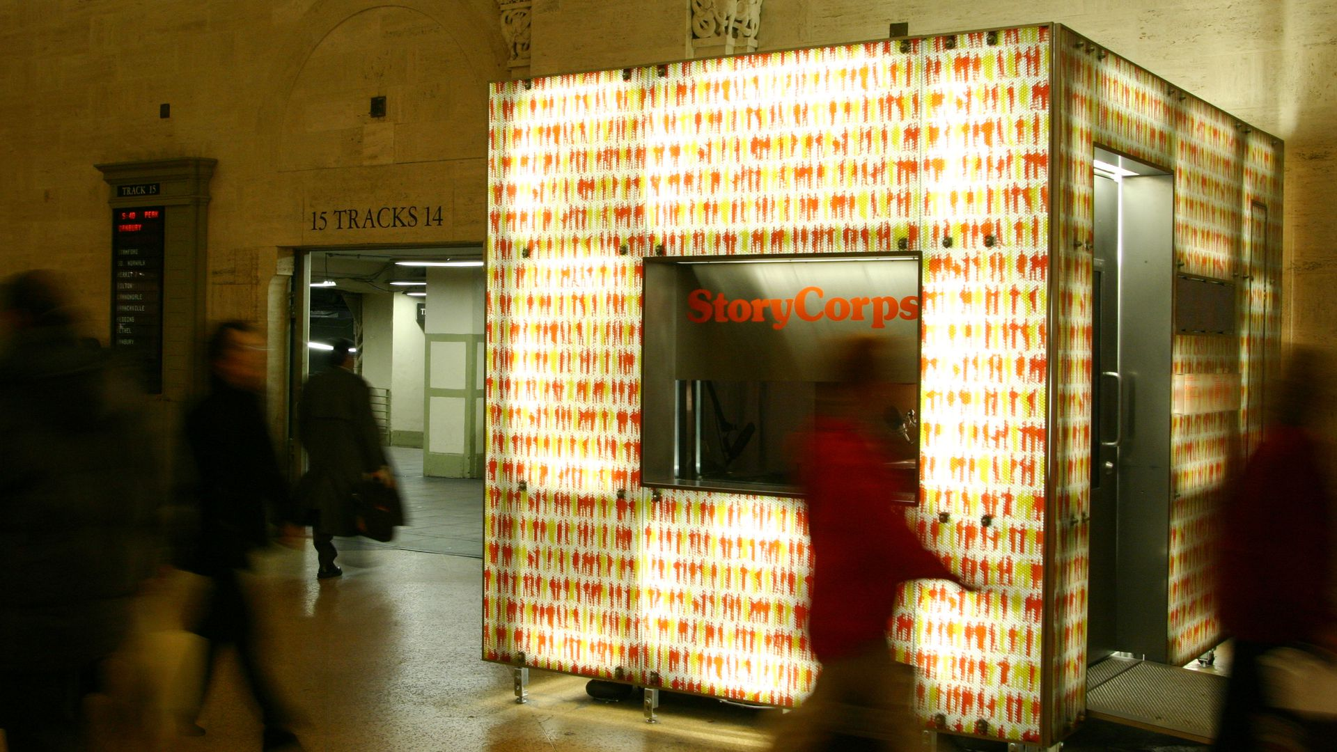 People in a train station walk by an illuminated both