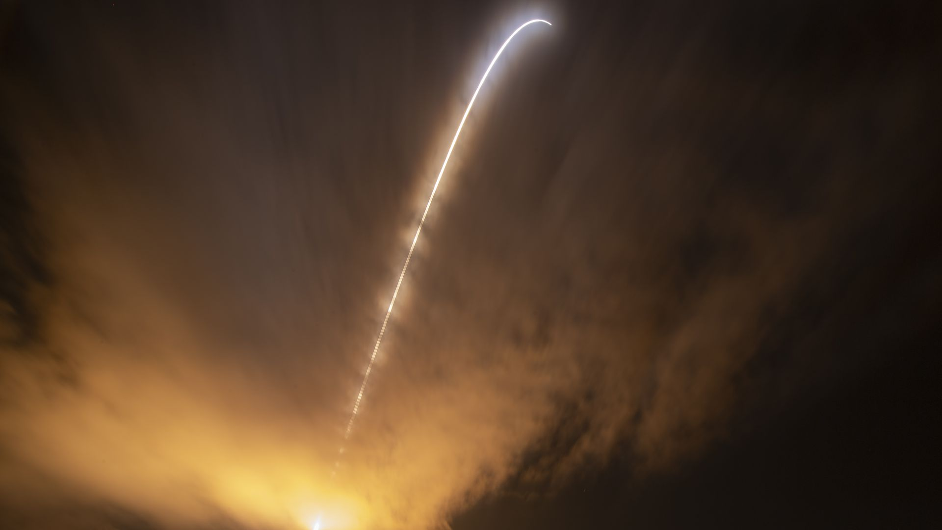 A rocket launches Nasa's Parker Solar Probe. It appears as a streak of light in a dark and gold sky.