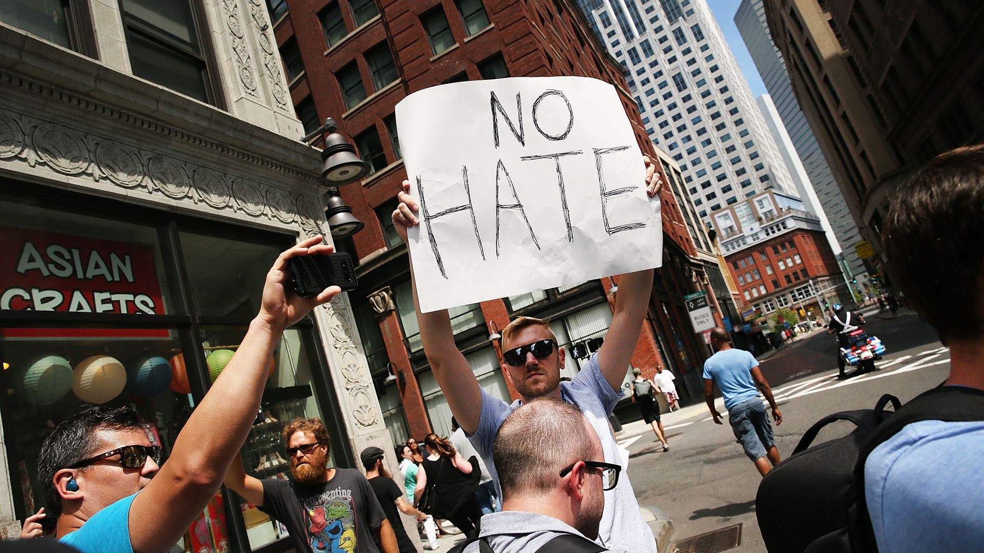 "A counter-protestor in Boston holds a sign that reads ""No hate"""