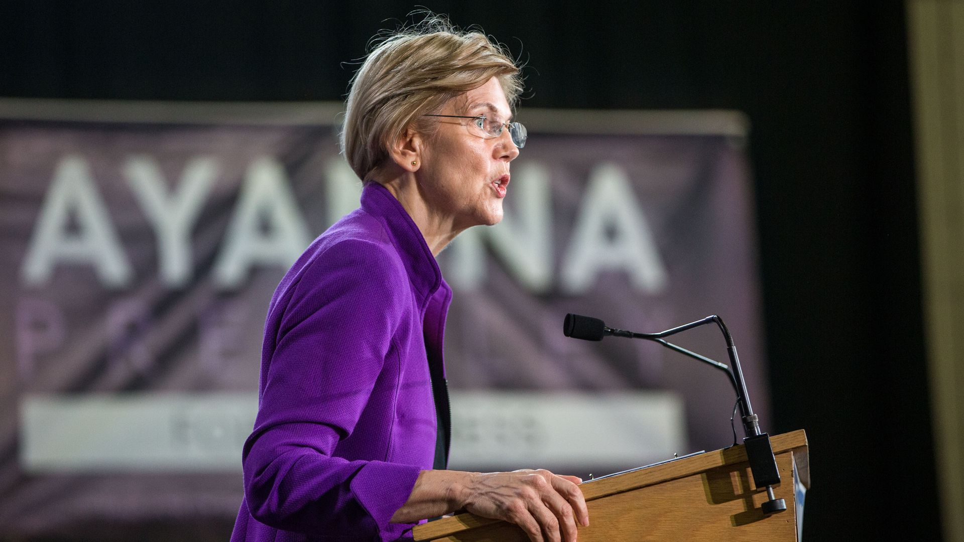 Elizabeth Warren stands at a podium on stage.