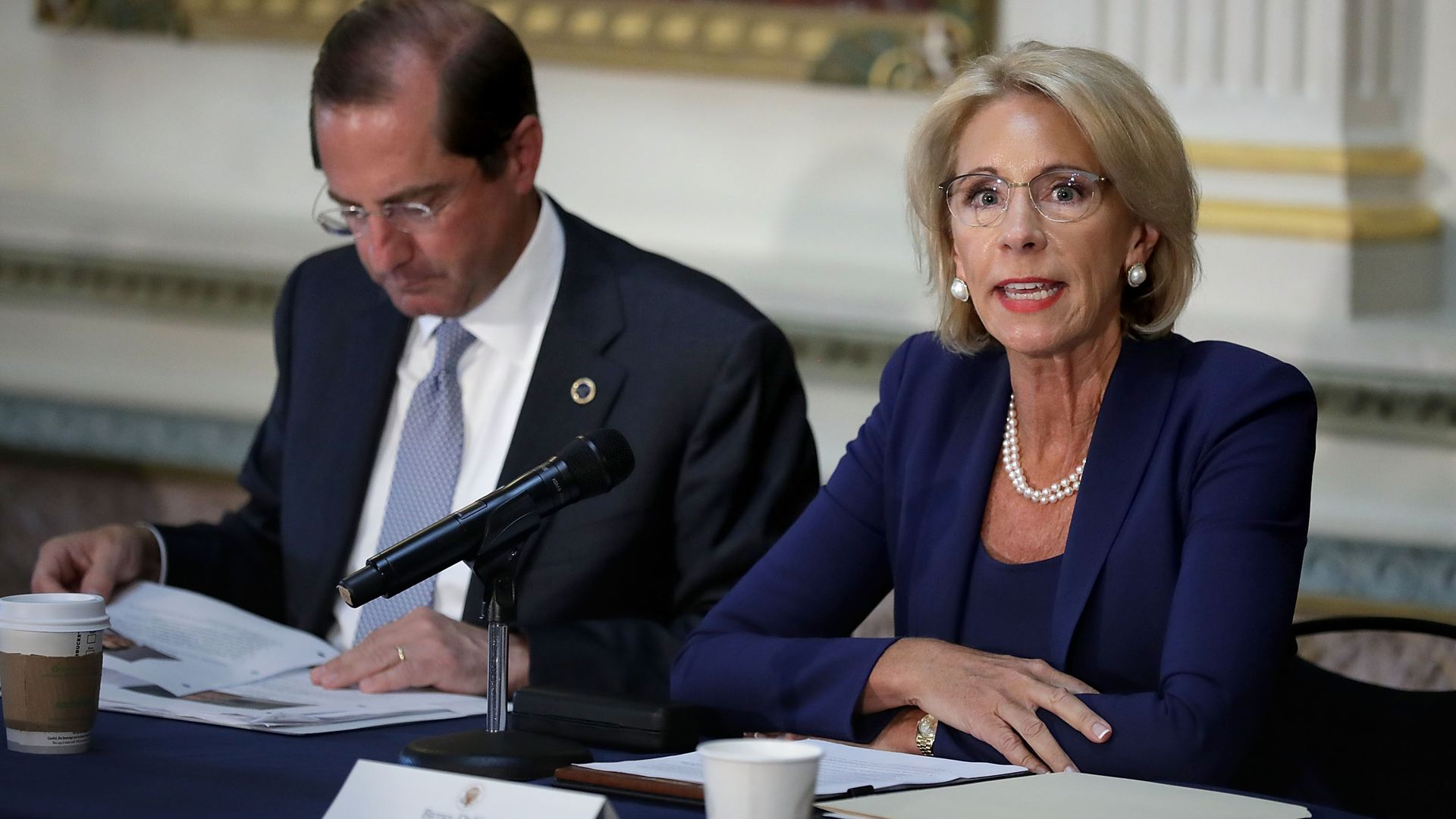Education Secretary Betsy DeVos sitting at a table.