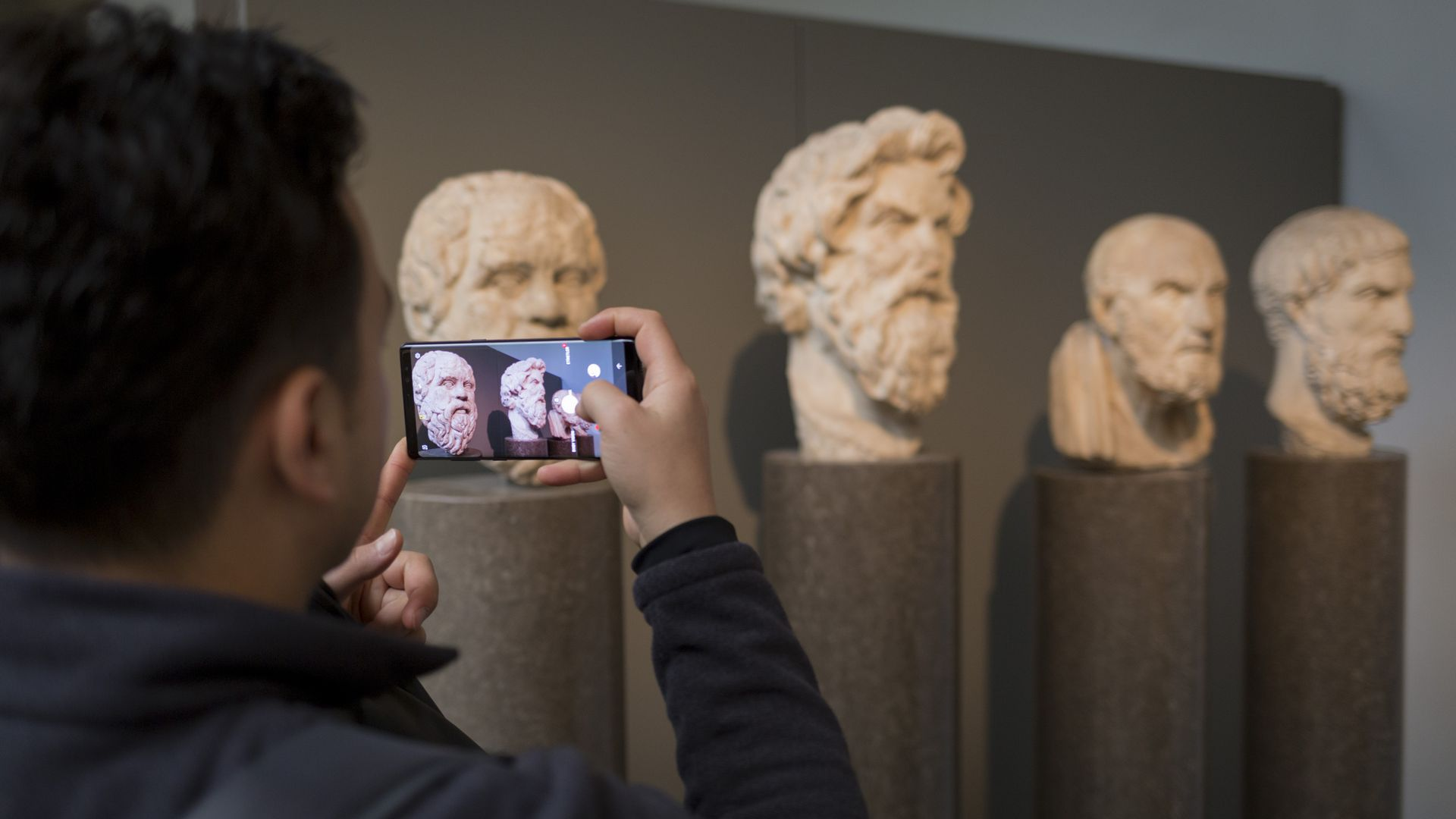 A visitor to the British museum takes a photo on his smartphone.