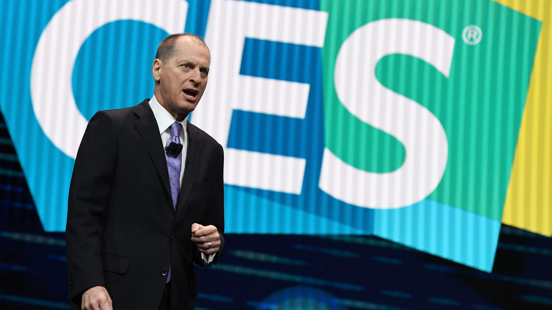 Gary Shapiro wears a suit on stage, in front of a CES logo
