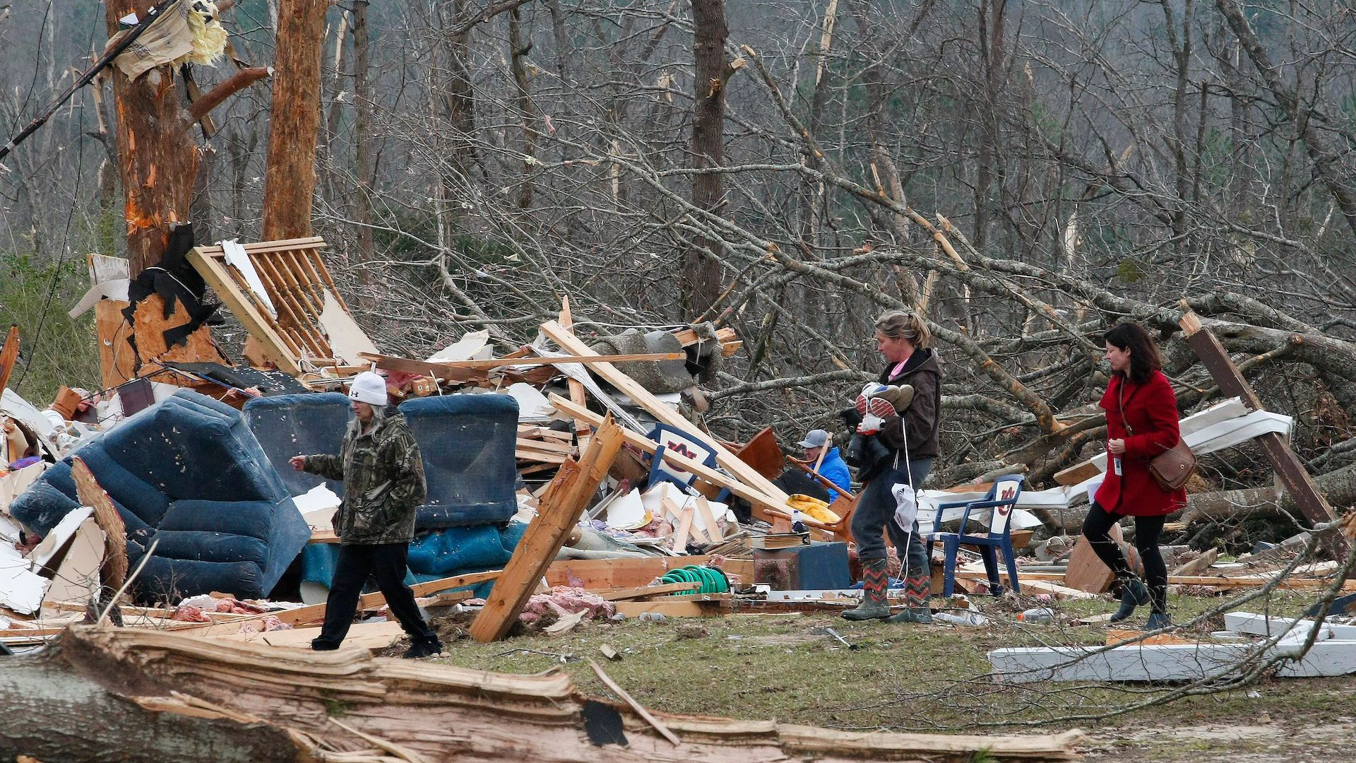 Residents look for belongings March 4, 2019 at a home after a tornado in Beauregard, Alabama.