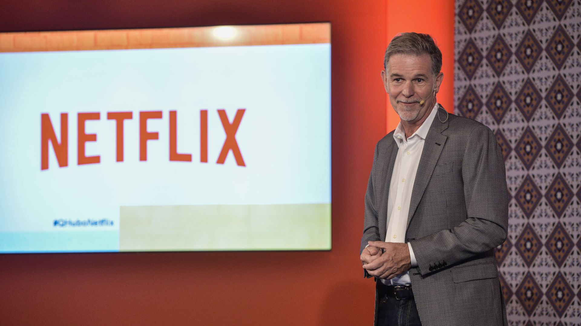 Reed Hastings standing on a stage with the Netflix logo on a screen in the background.