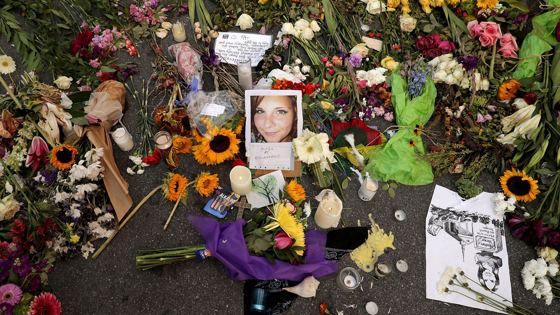 Flowers, candles and chalk-written messages surround a photograph of Heather Heyer on the spot where she was killed and 19 others injured.