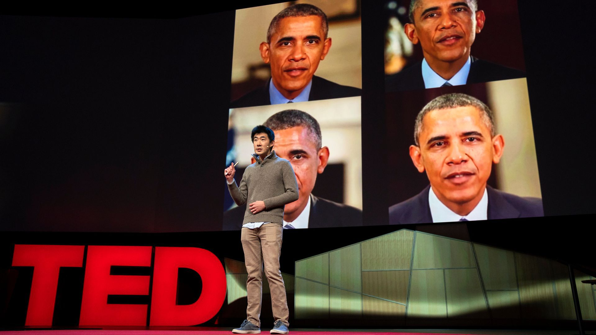 Supasorn Suwajanakorn speaks on stage at TED2018 with photos of Barack Obama on the screen behind him