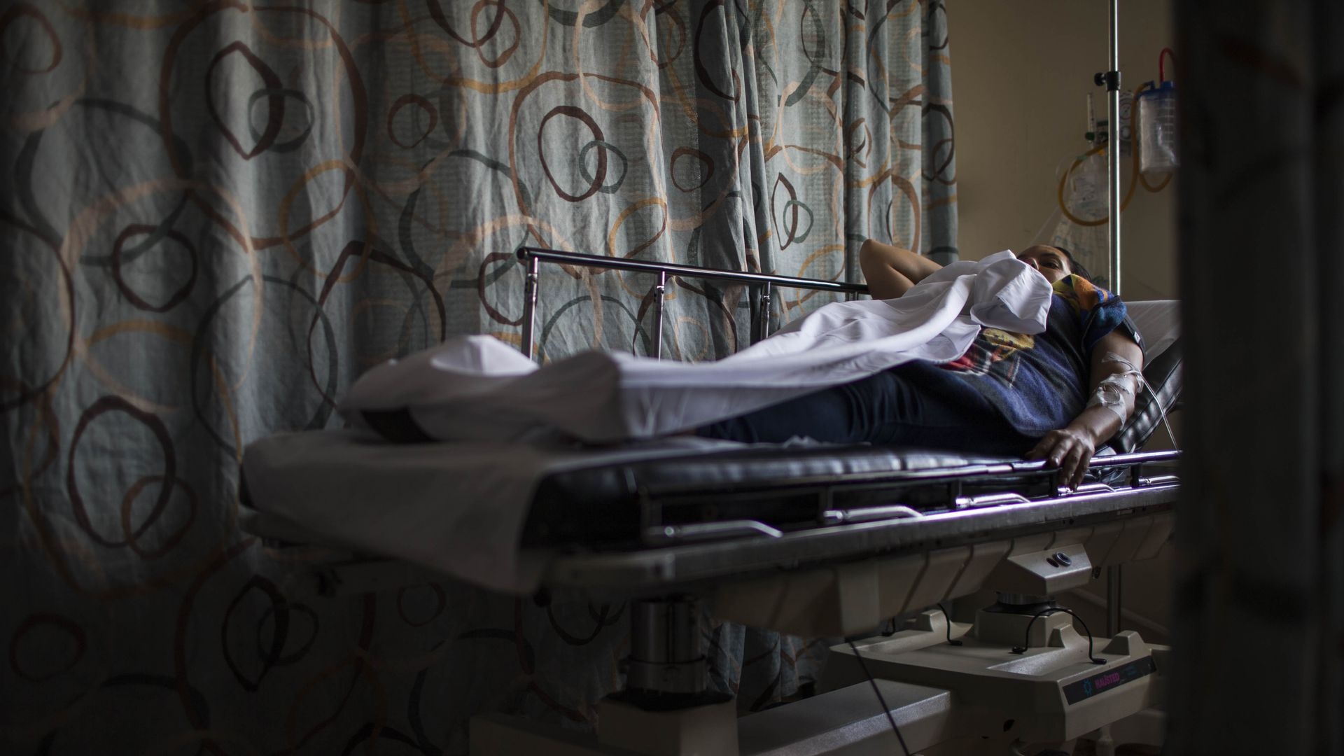 A patient rests in a hospital emergency room.