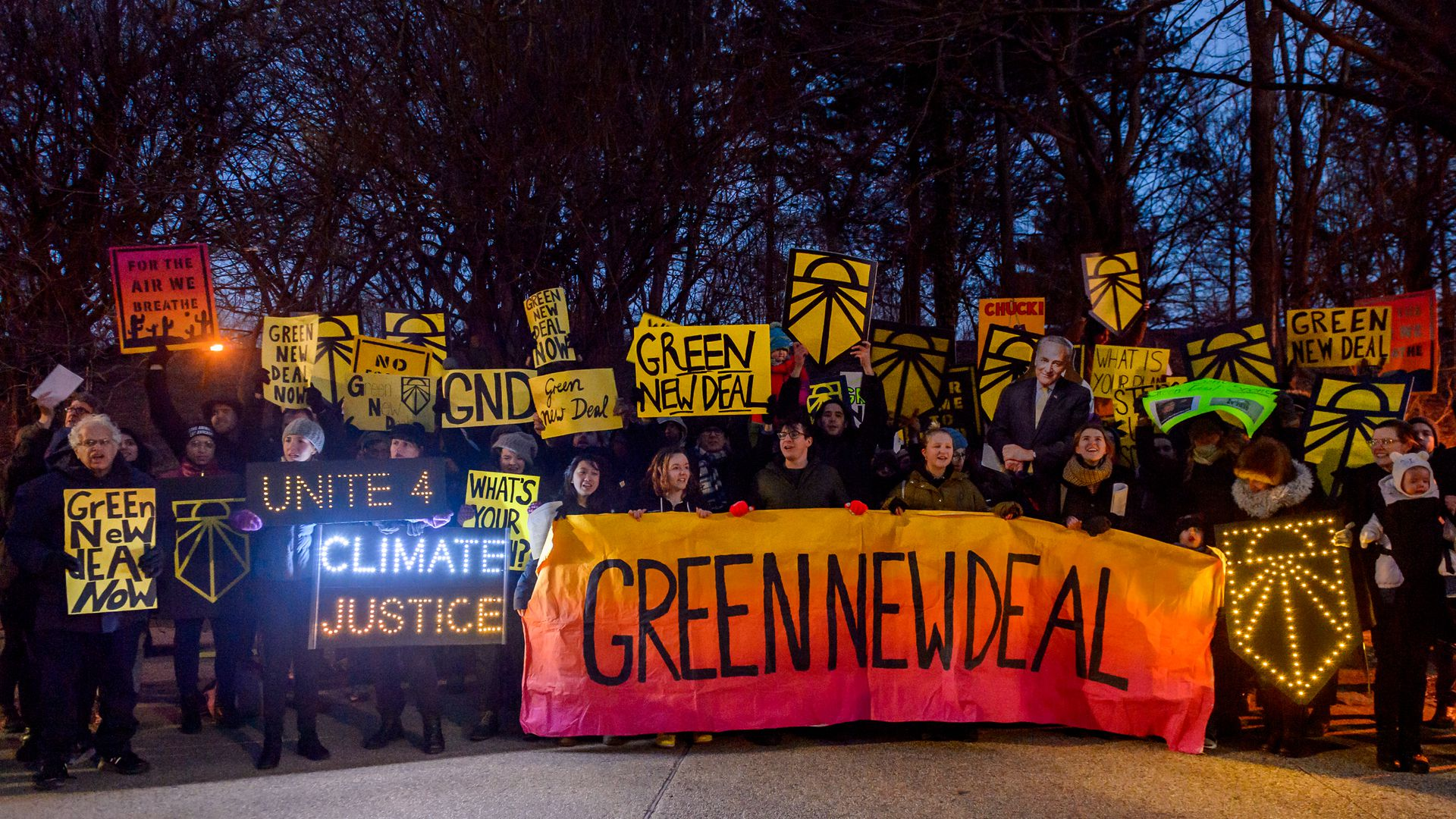 "In this image, a line of demonstrators holding various signs support an orange banner that says ""Green New Deal."""
