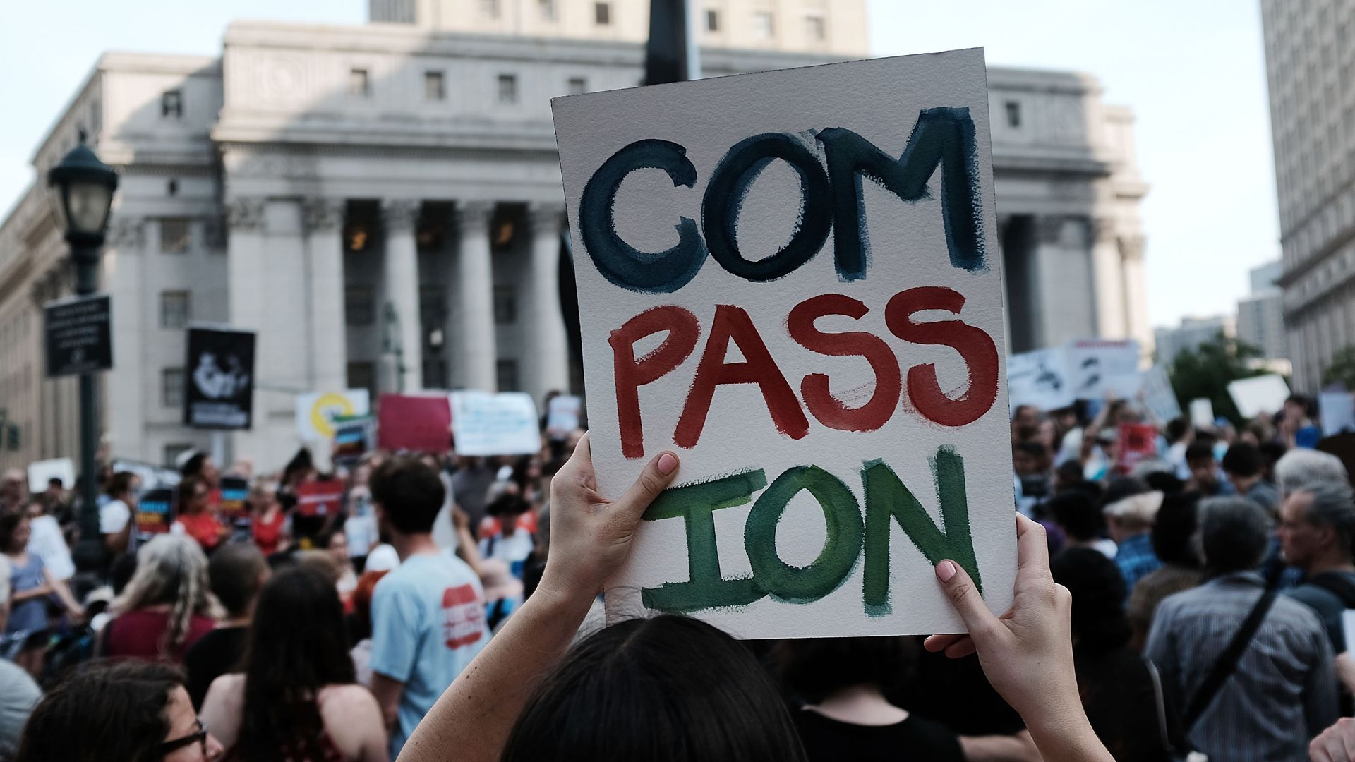 "Protester holds sign reading ""Compassion"""