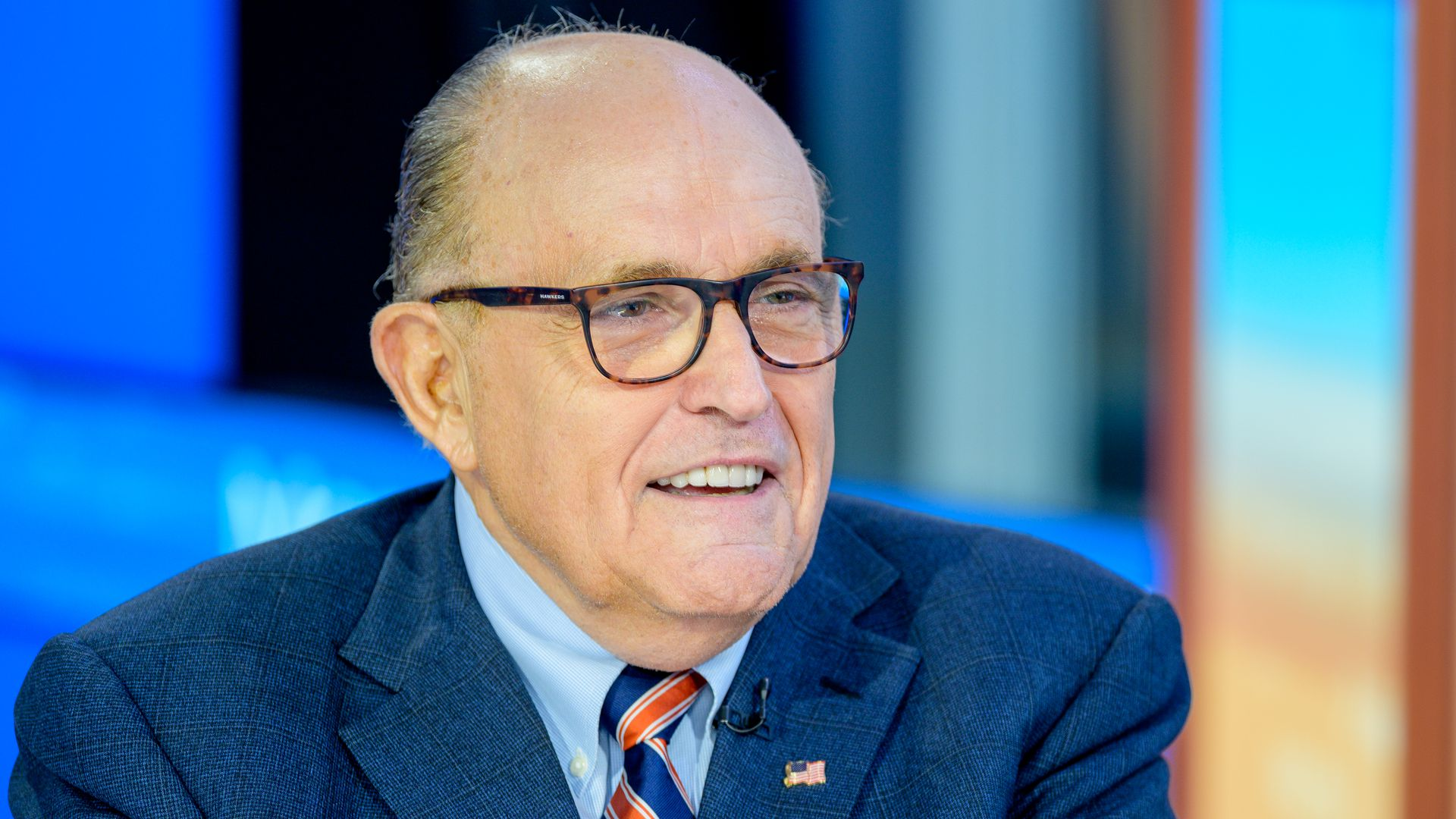In this image, Giuliani wears a suit and glasses and smiles