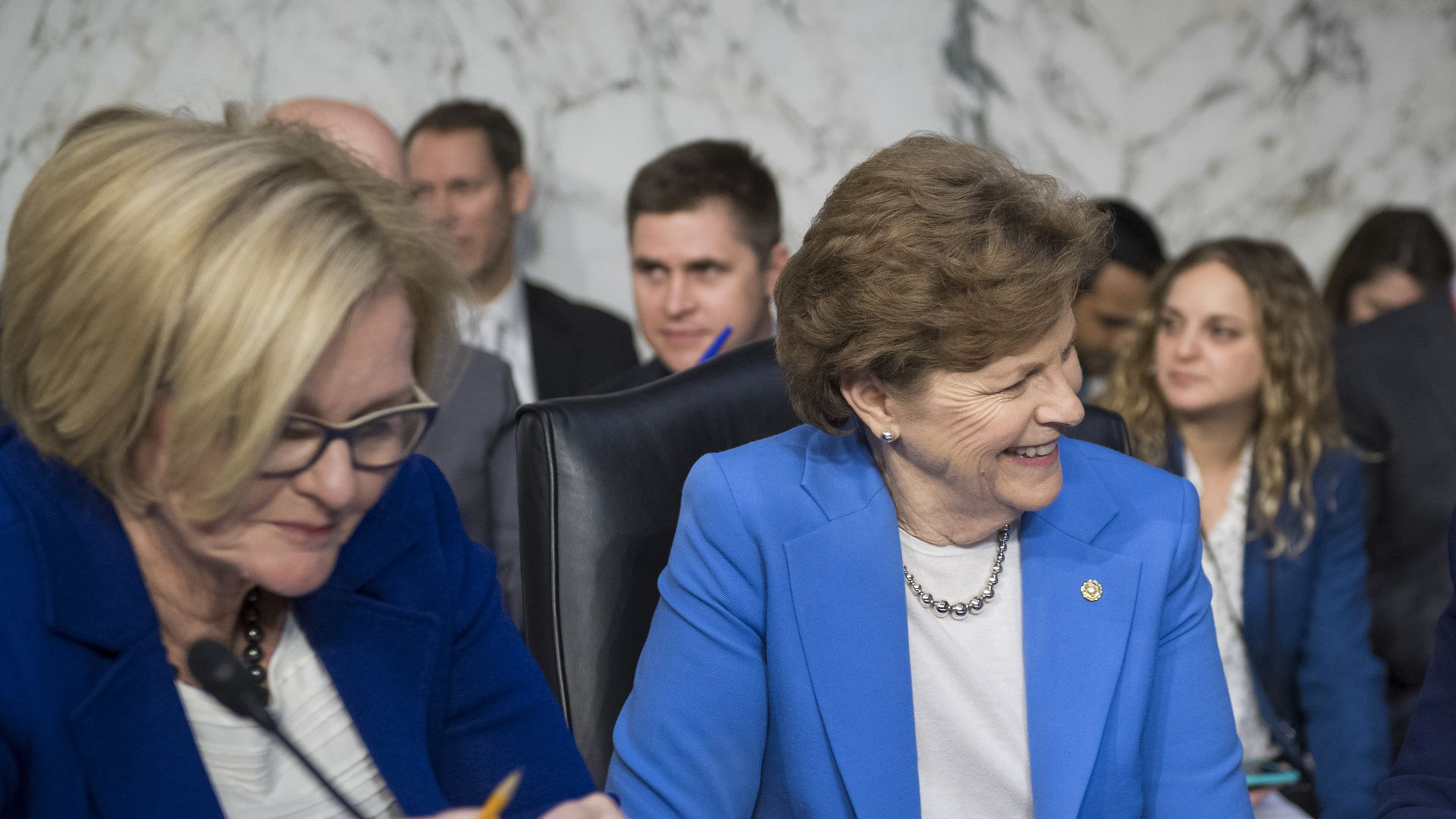 Senator McCaskill looks down at a desk and Senator Shaheen smiles.
