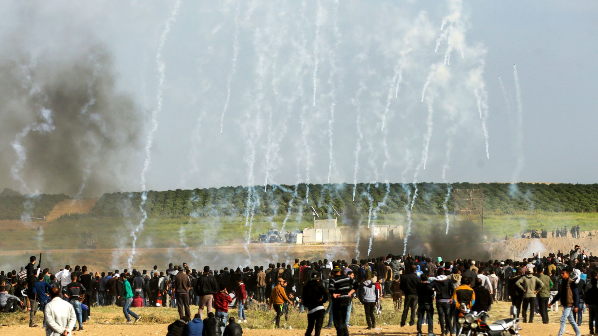 Palestinian protestors run for cover from tear gas fired by Israeli security forces during clashes following a demonstration commemorating Land Day, near the border with Israel