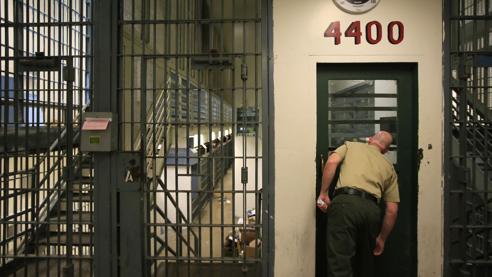 A sheriff peers into jail cells.