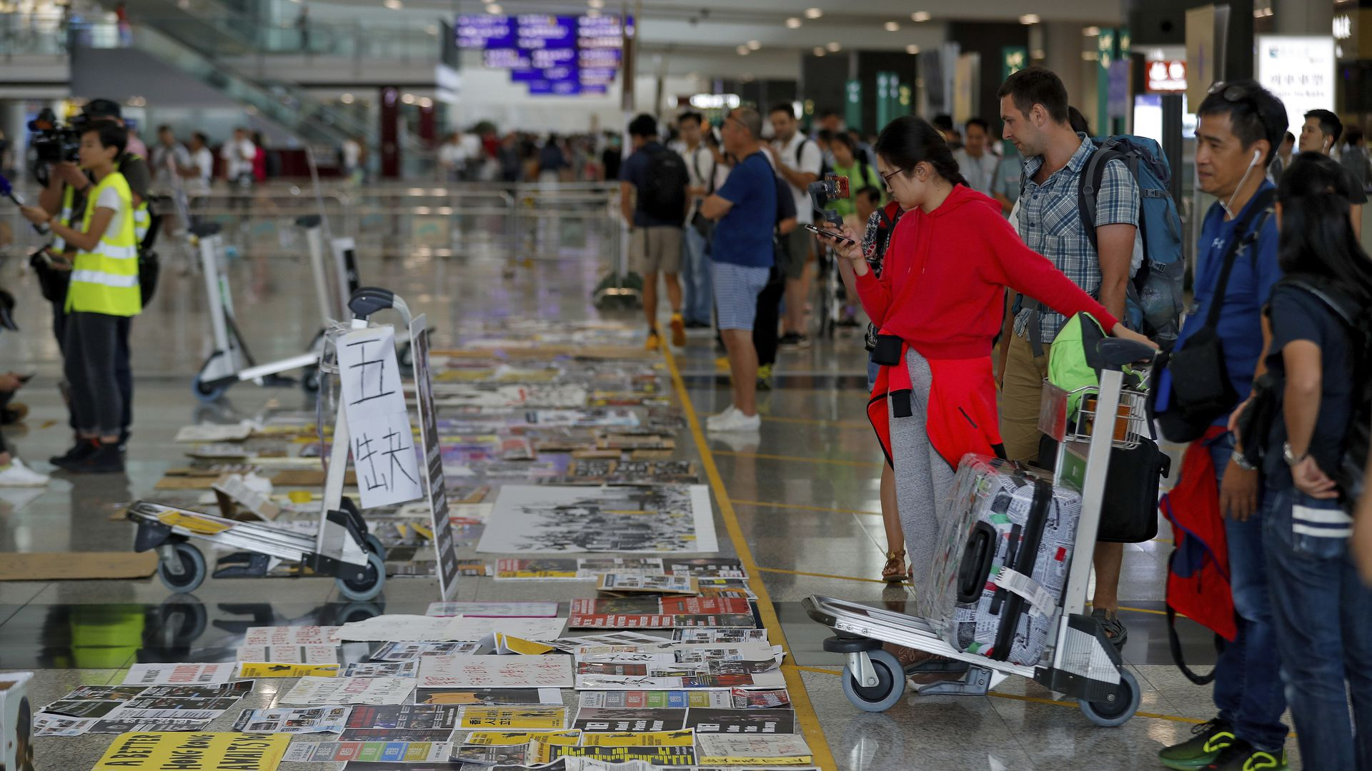 Travellers look at placards and posters placed by protesters at the airport in Hong Kong