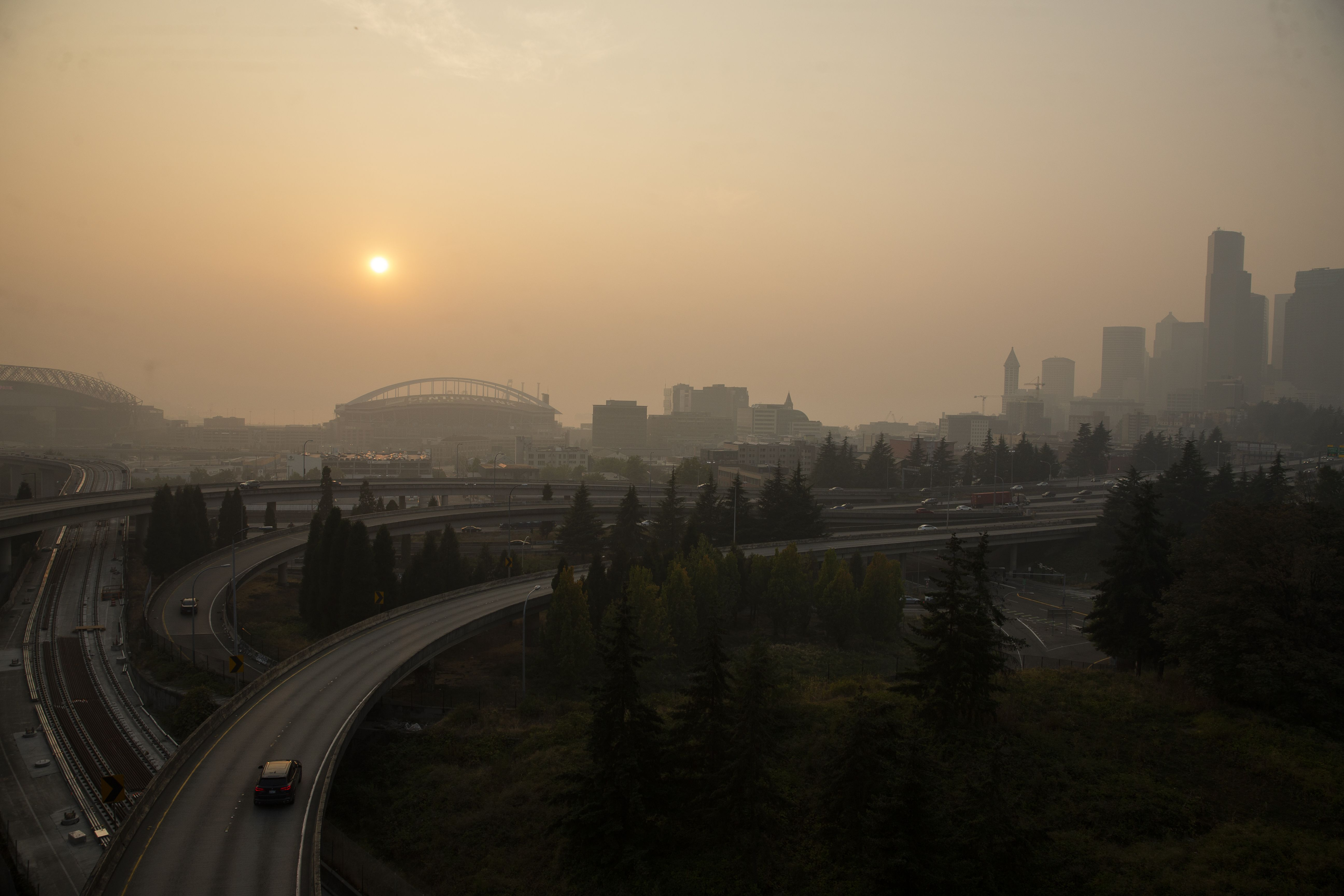 Cars drive on I-5 in front of a hazy Seattle skyline due to wildfire smoke on September 11, 2020 in Seattle, Washington.