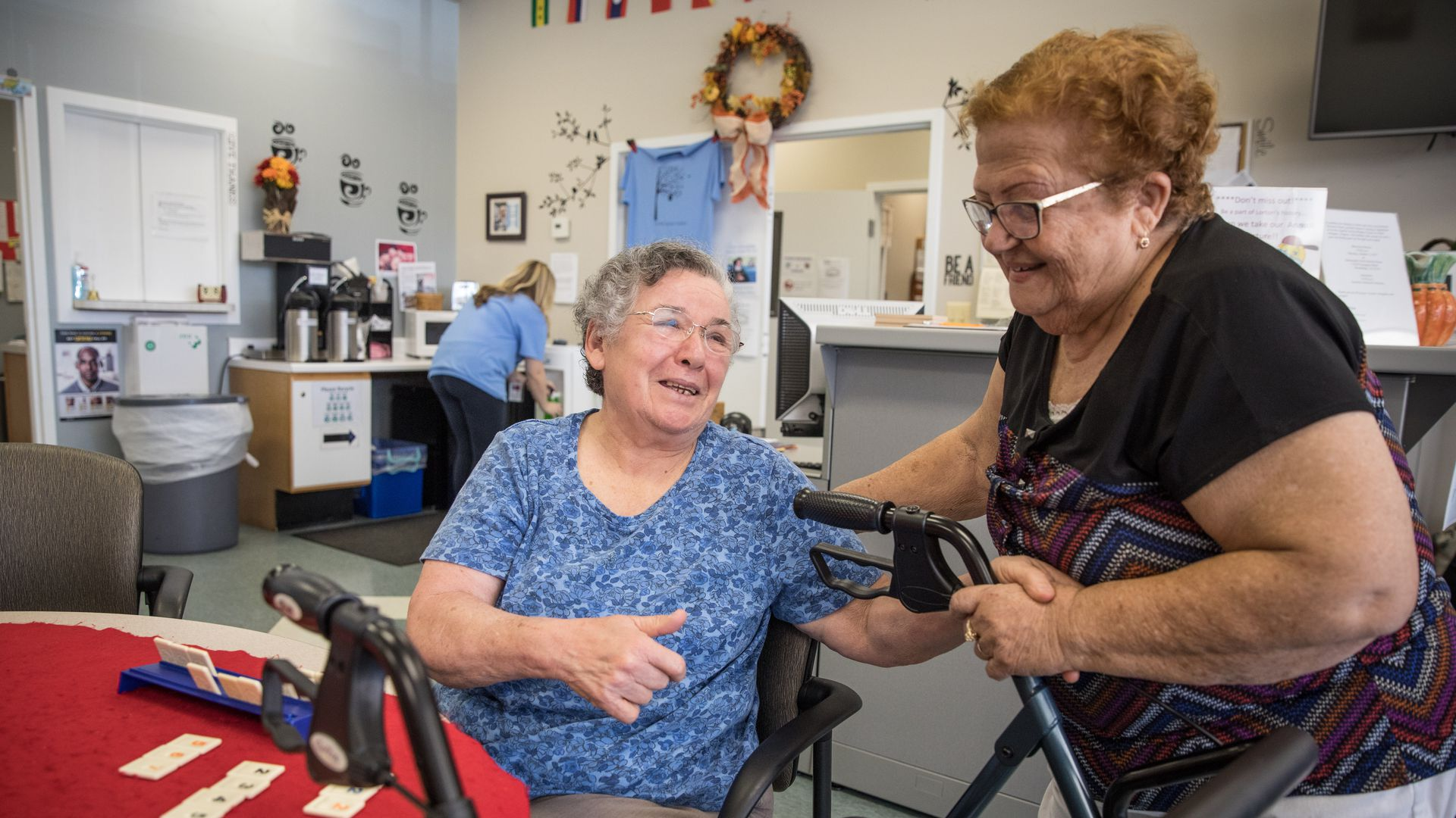 Two older women sit near a table at a senior center.
