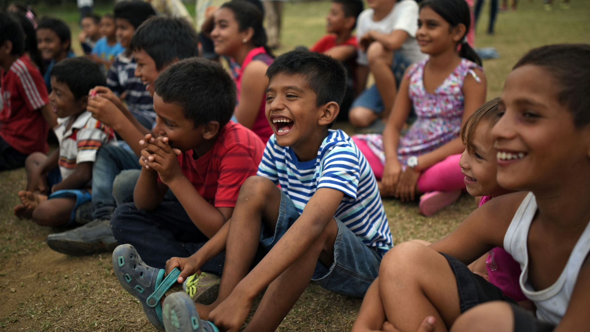Central American migrant children laugh at a show put on by a clown.