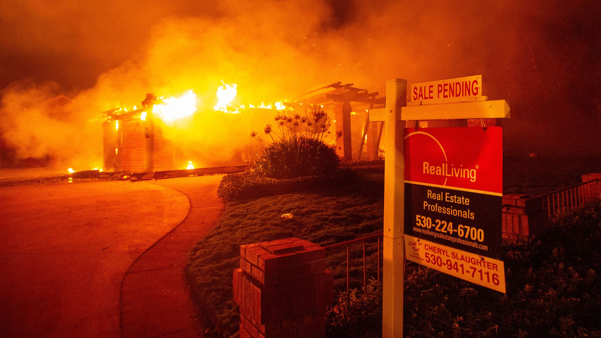 A real estate sign sits in front of a burning structure in Redding, California.