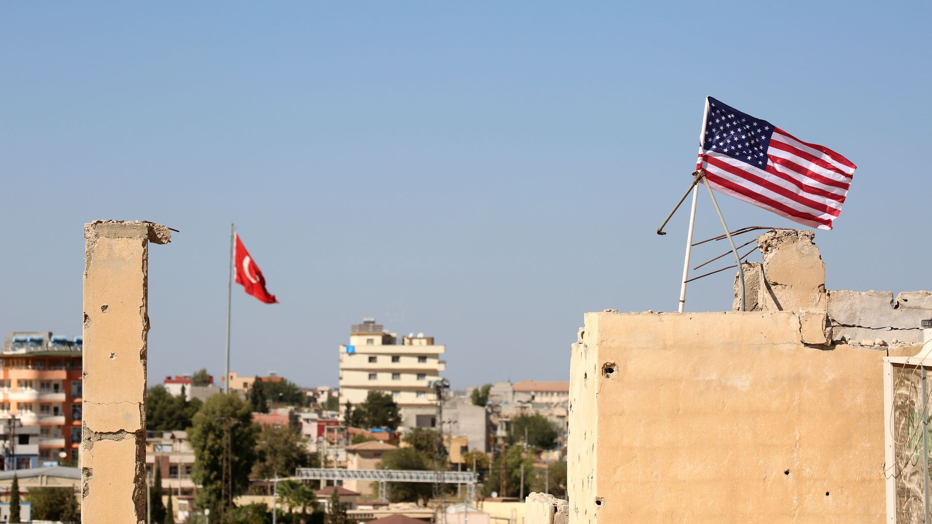 A picture taken on September 17, 2016 shows an American flag (R) fluttering above a building used by the Kurdish police known as the Asayish, in the Syrian town of Tal Abyad.