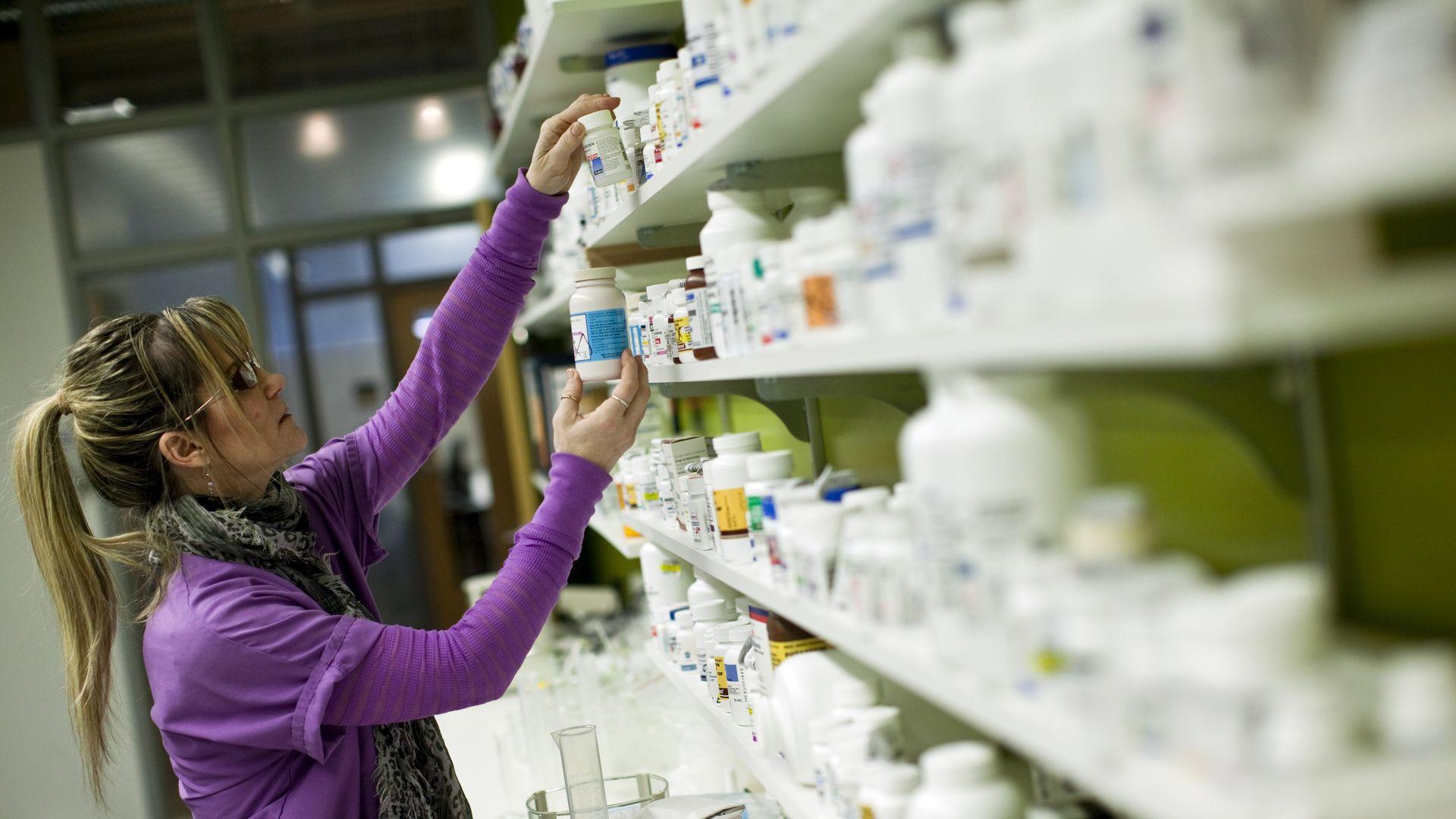 A pharmacy technician looks at prescription pill bottles on shelves.