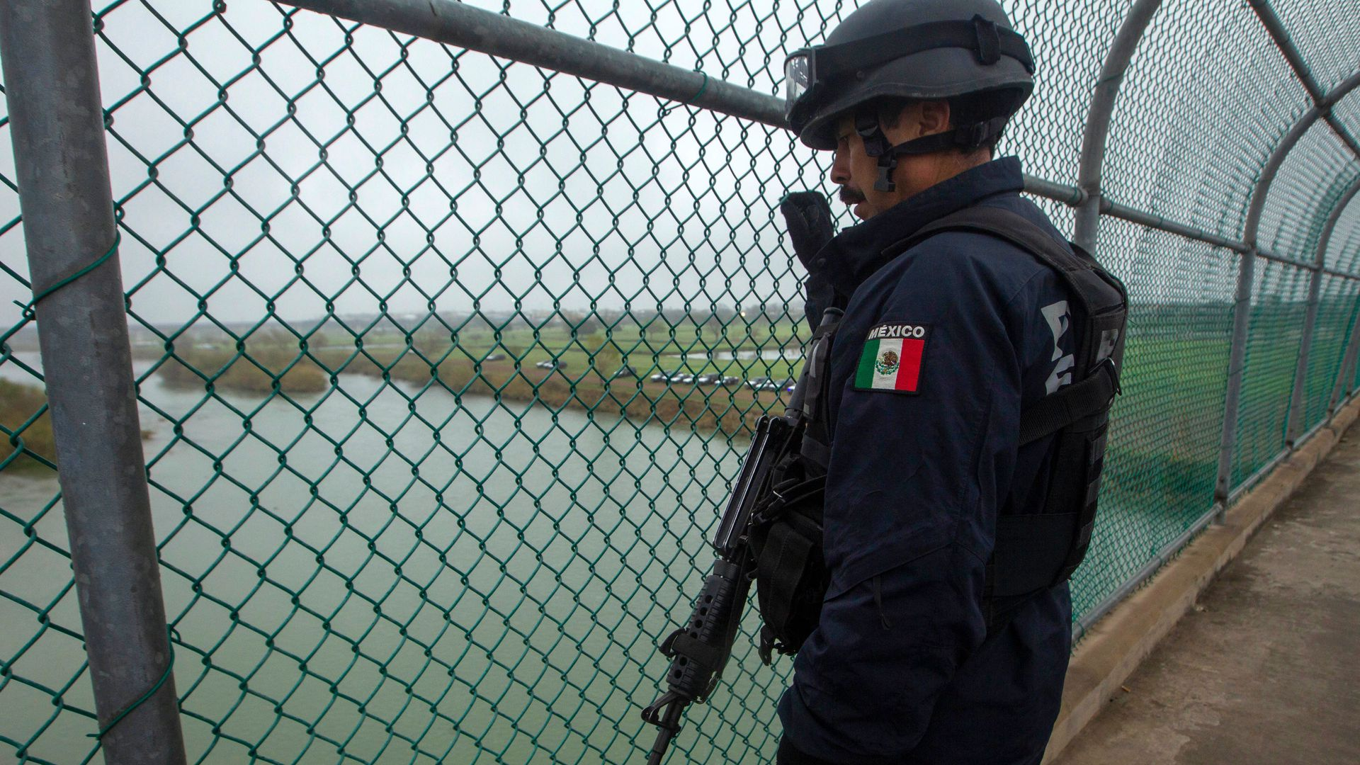 A Mexican Federal Police officer guards an international bridge between Mexico and Texas