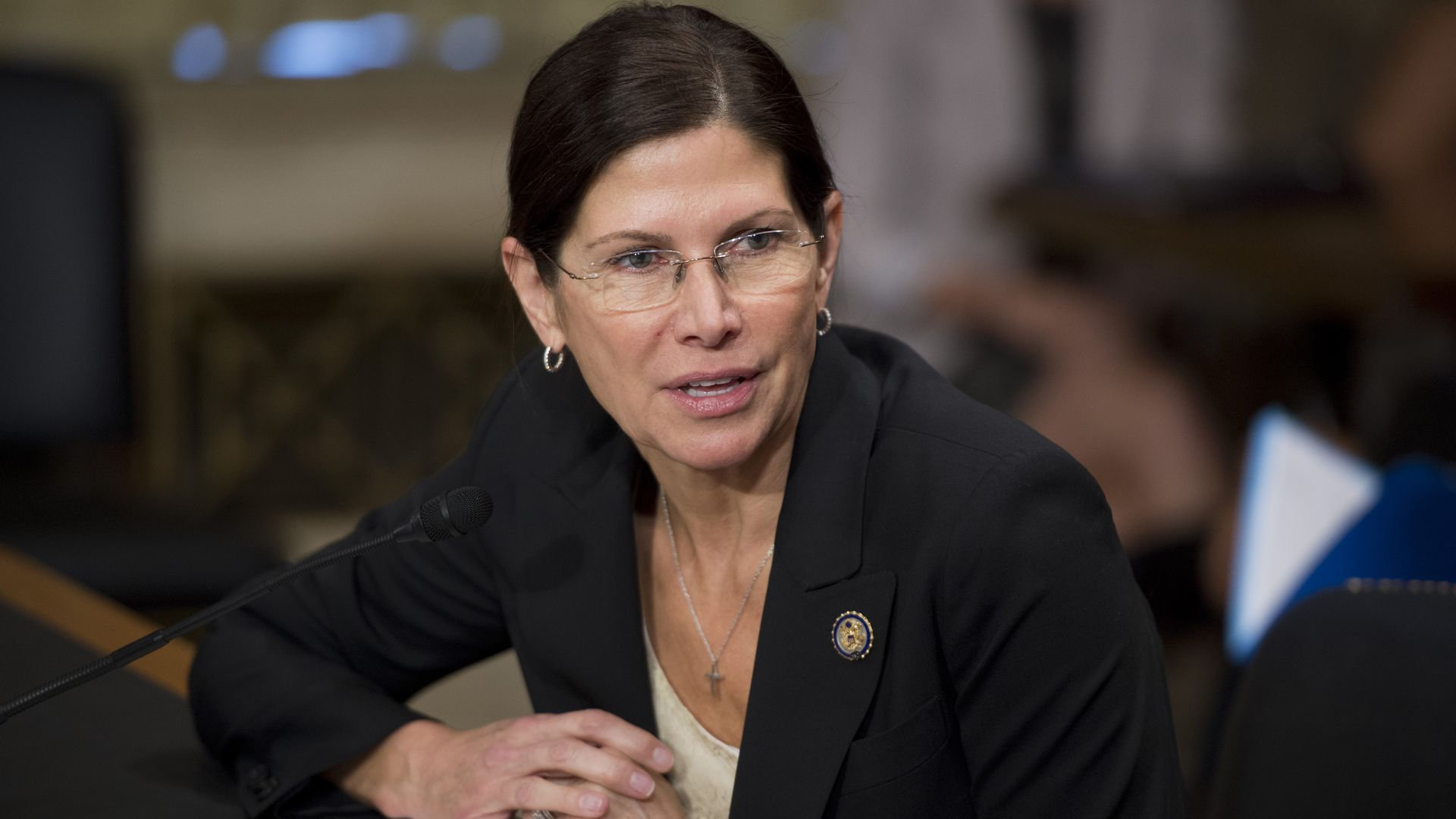 Mary Bono sitting in the house of representatives with suit and glasses on.