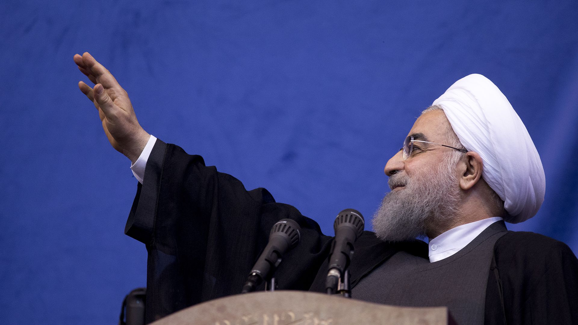 Hassan Rouhani waves his hand up before a blue background.