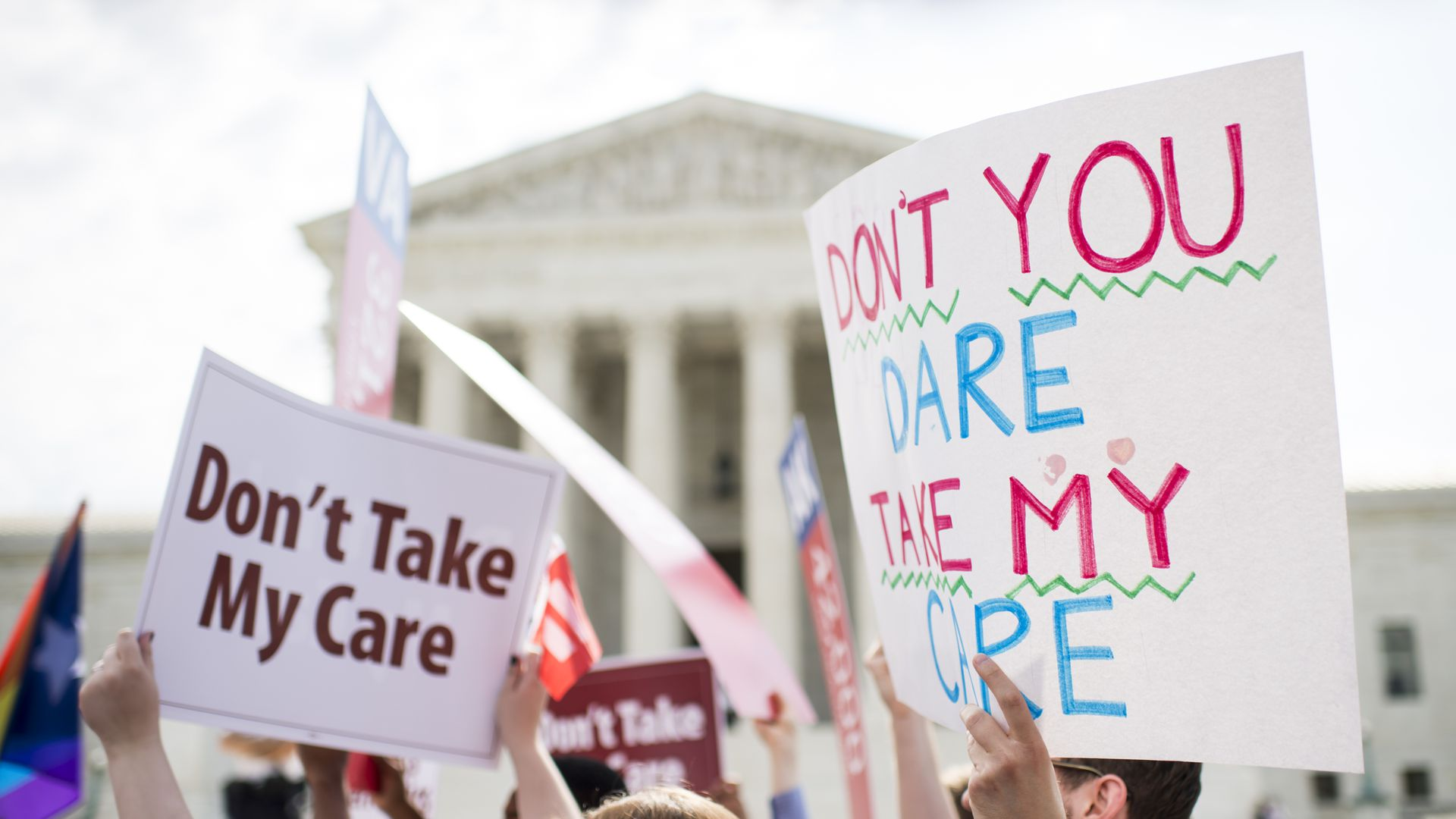 Affordable Care Act supporters hold up signs outside the Supreme Court.
