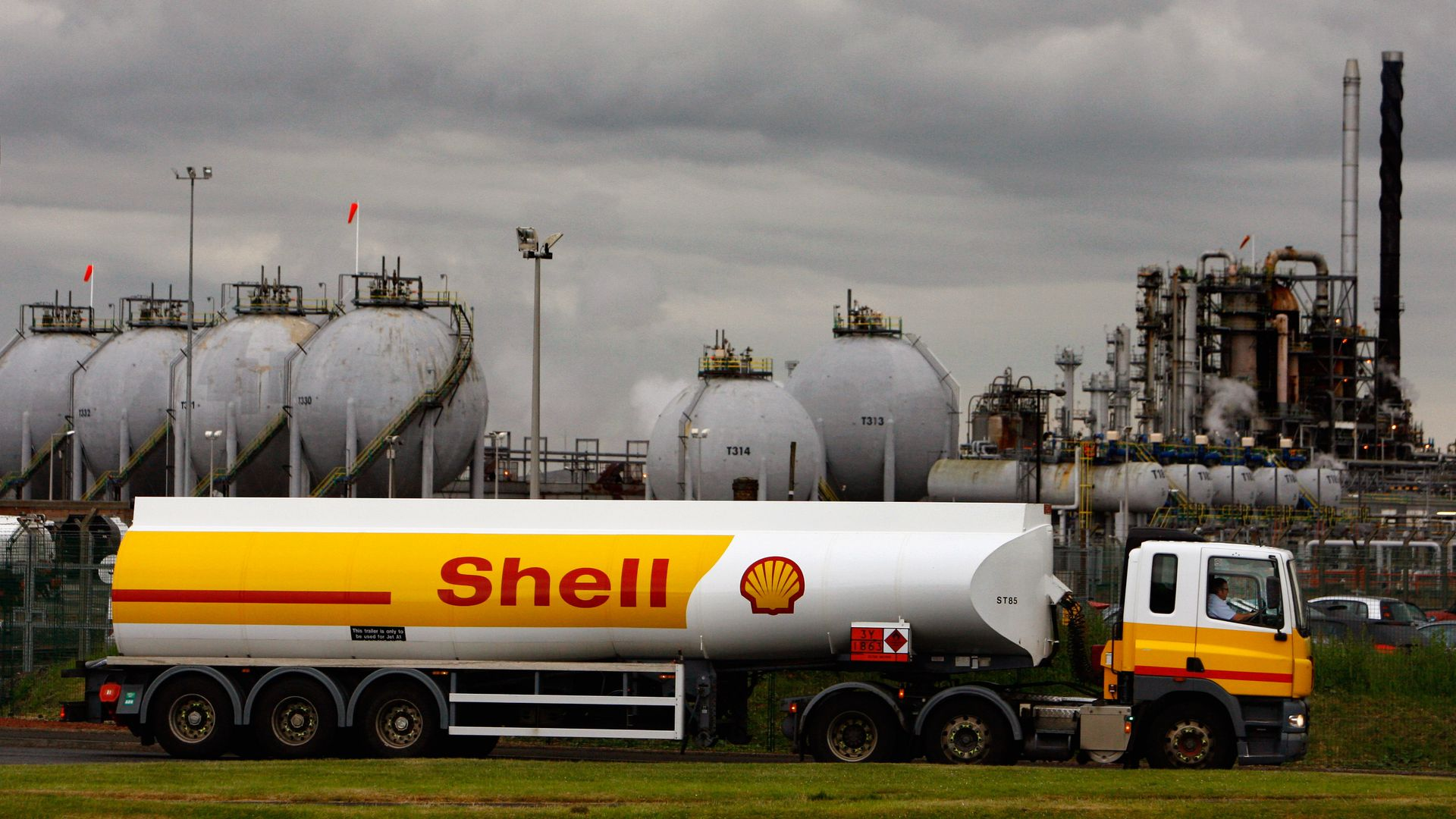 In this image, a Shell brand tanker sits in front of a plant on a cloudy day.
