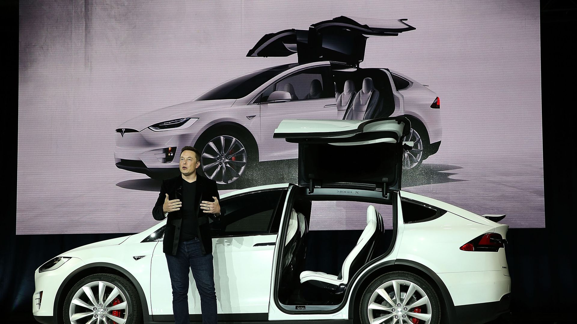Elon Musk speaking in front of Tesla car