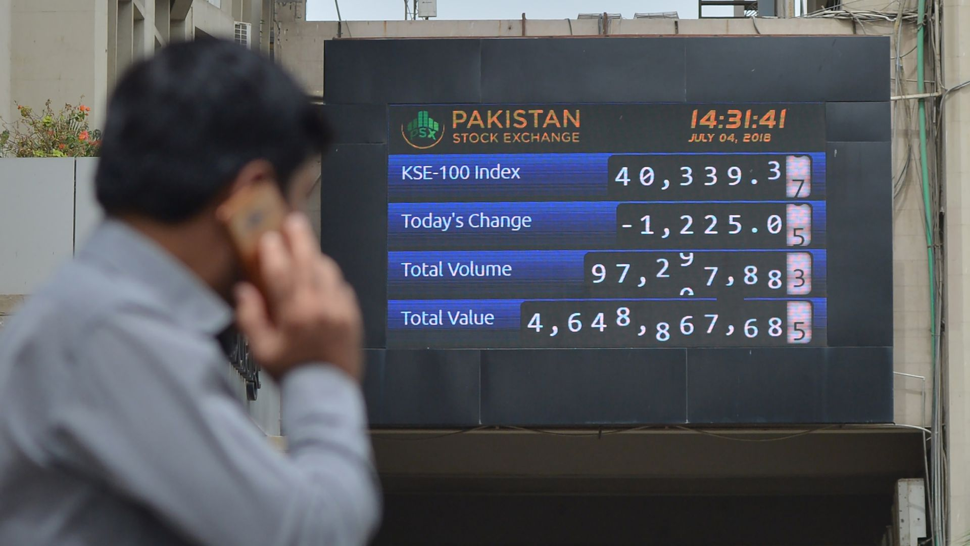 A Pakistani stockbroker looks at an index board during a trading session at the Pakistan Stock Exchange