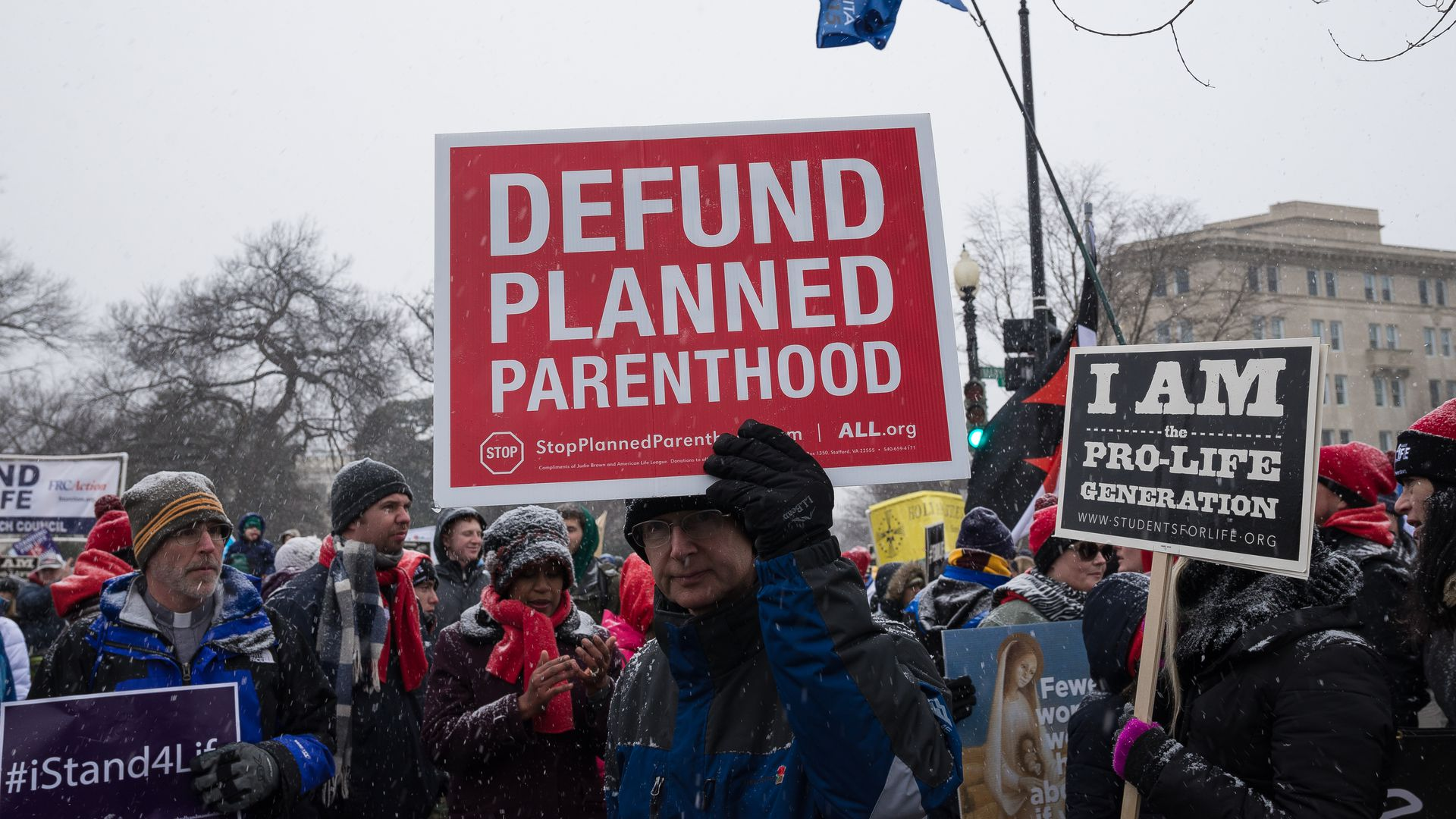"Protesters at the March for Life in Washington, carrying a placard that says ""Defund Planned Parenthood."""