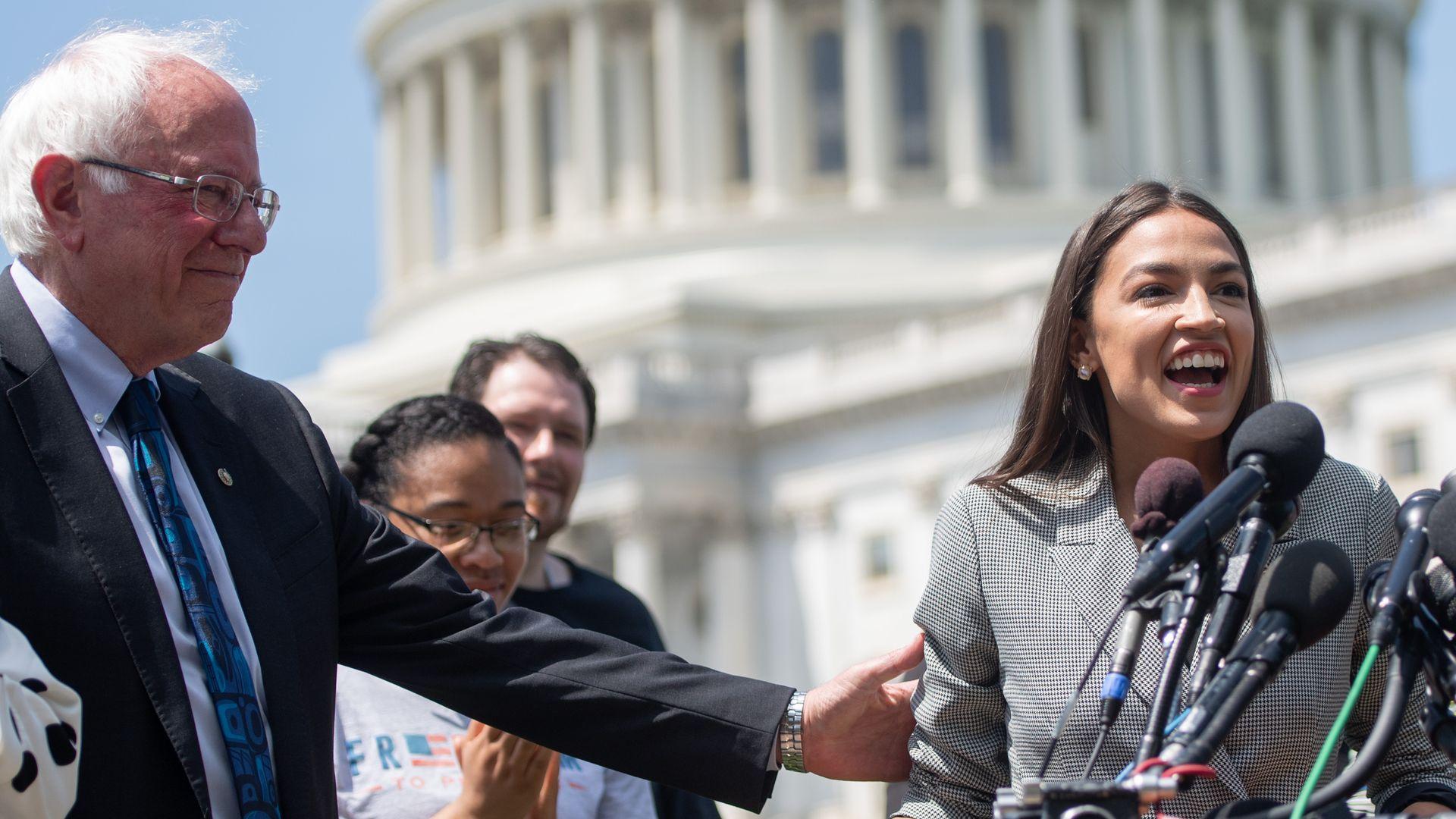 Representative Alexandria Ocasio-Cortez (2nd R), Democrat of New York, speaks alongside US Senator Bernie Sanders (2nd L), Independent of Vermont