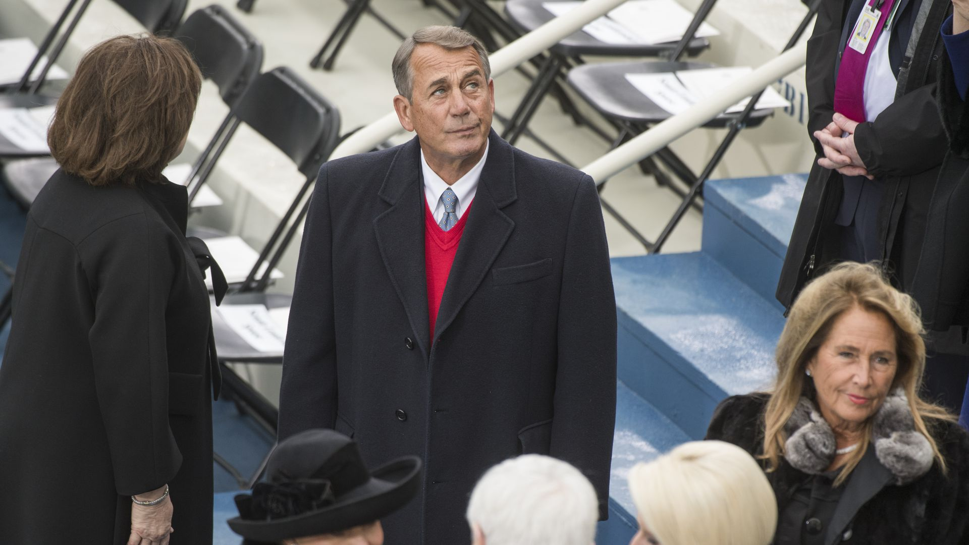 Boehner standing in a coat looking up