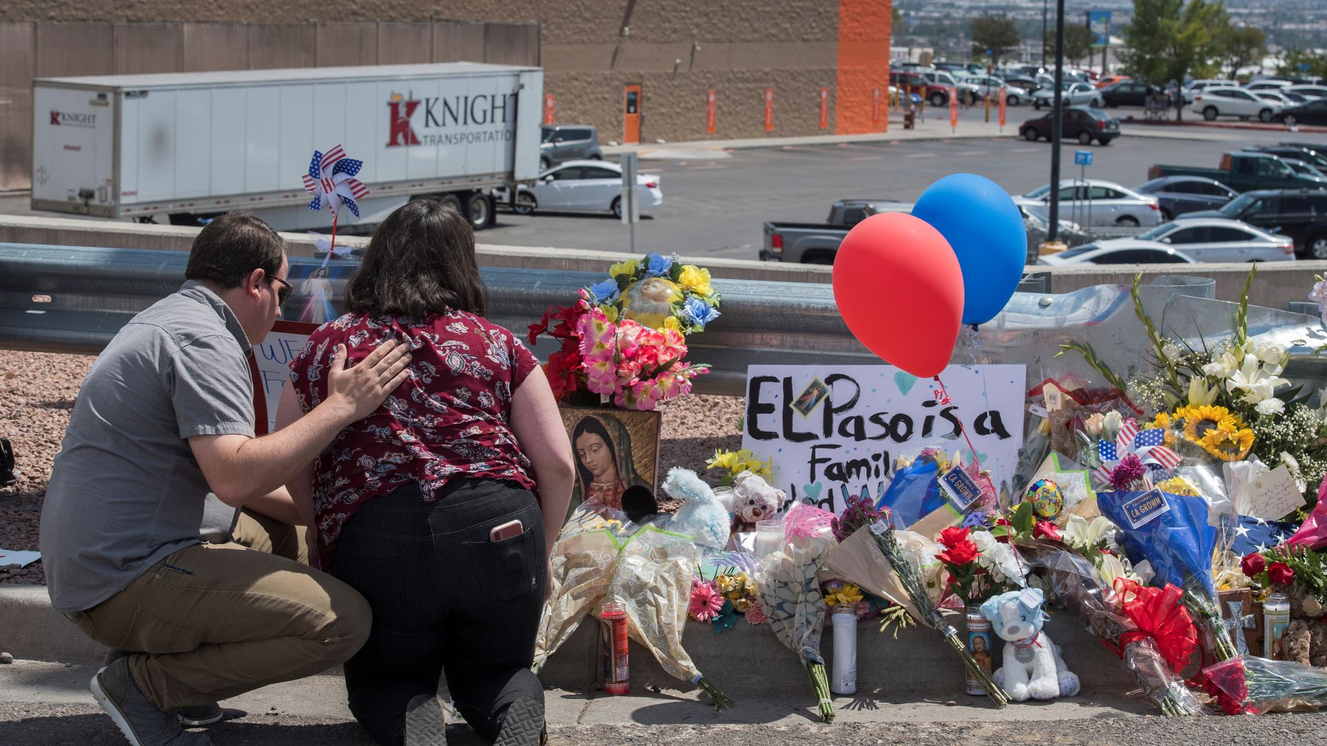 People pray beside a makeshift memorial outside the Cielo Vista Mall Wal-Mart (background) where a shooting left 20 people dead in El Paso, Texas, on August 4, 2019.