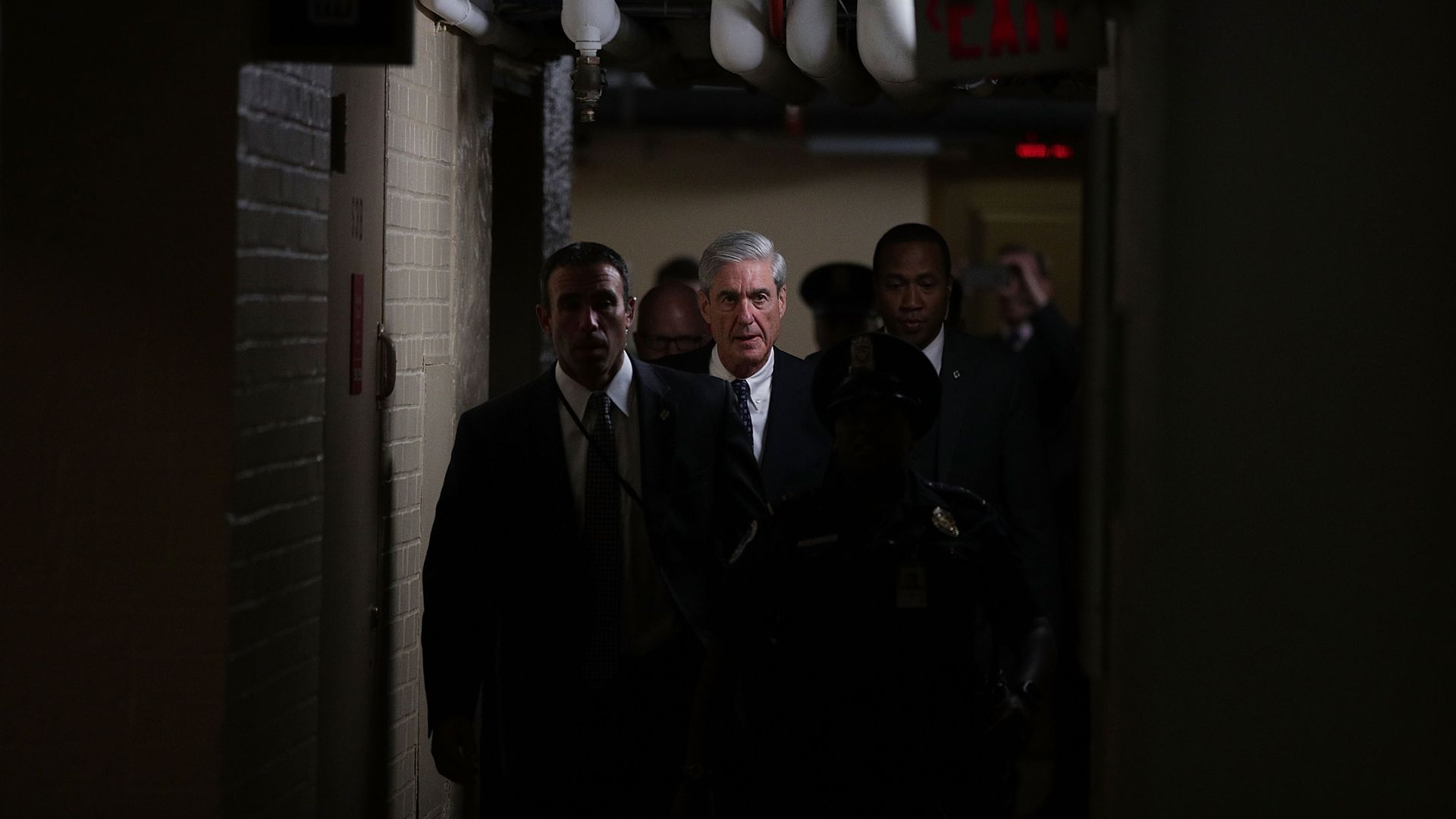 Robert Mueller is illuminated as he walks down a hallway at the Capital surrounded by security guards