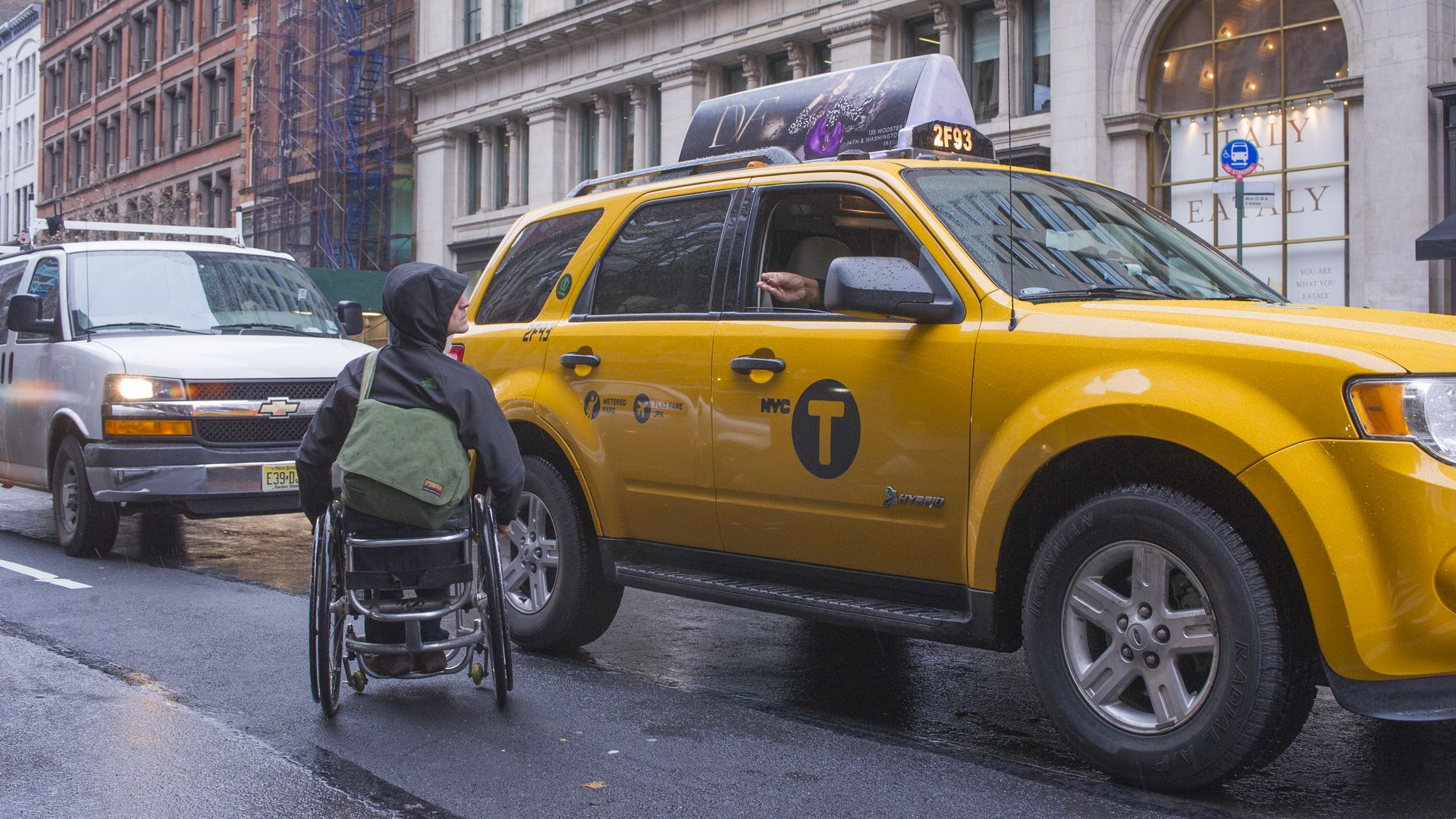 A man in a wheelchair hails a taxi