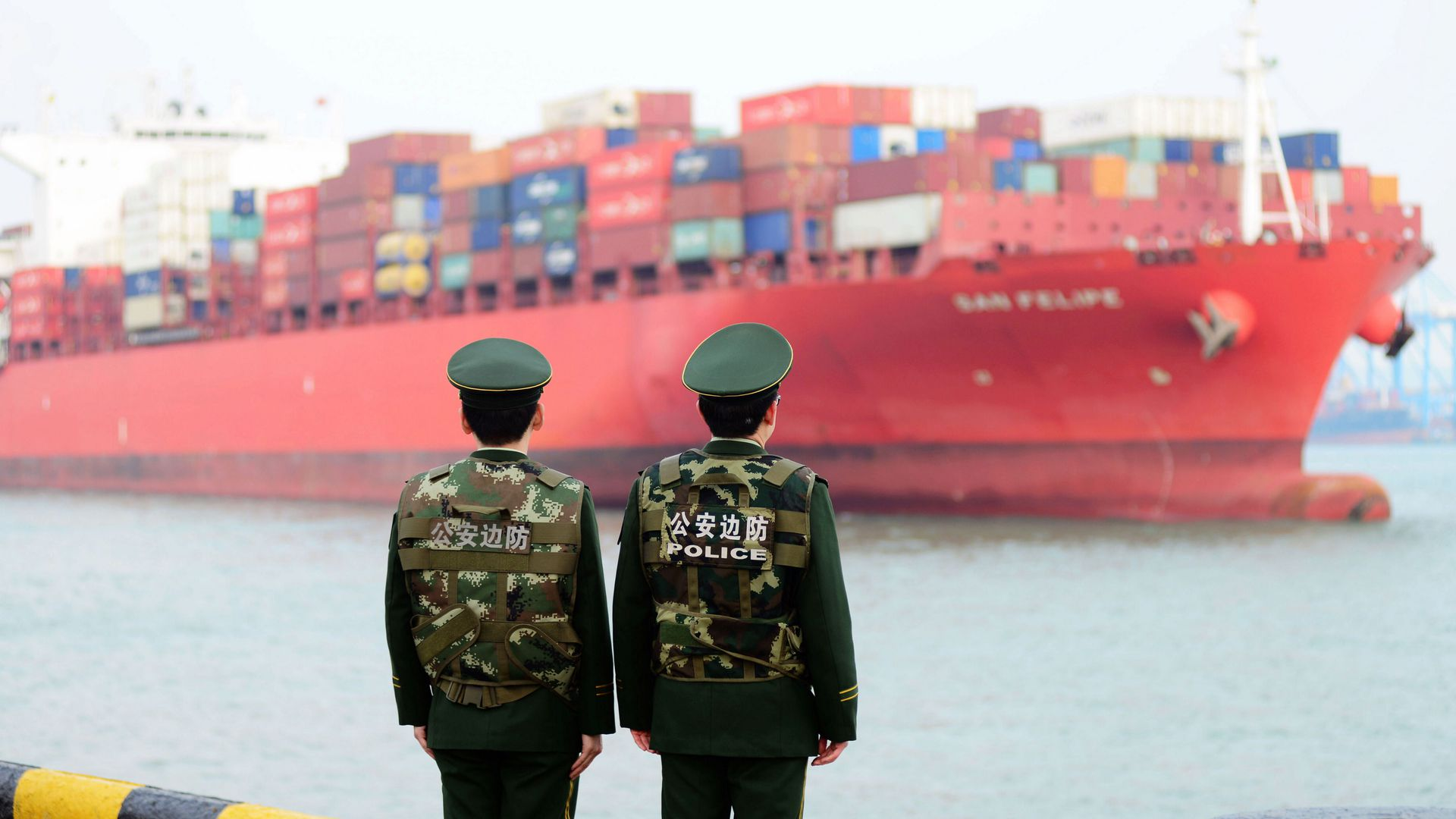 Two Chinese policemen look at the harbor where they wait for a large containership arrive