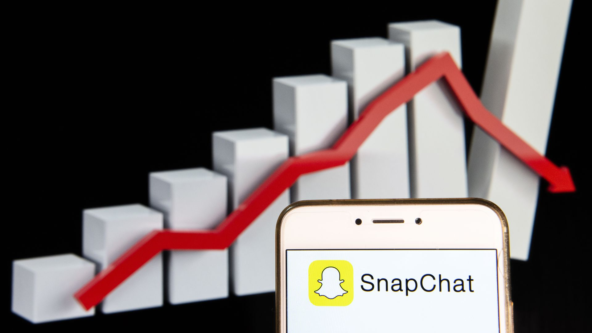 illustration of snap logo in front of declining line graph