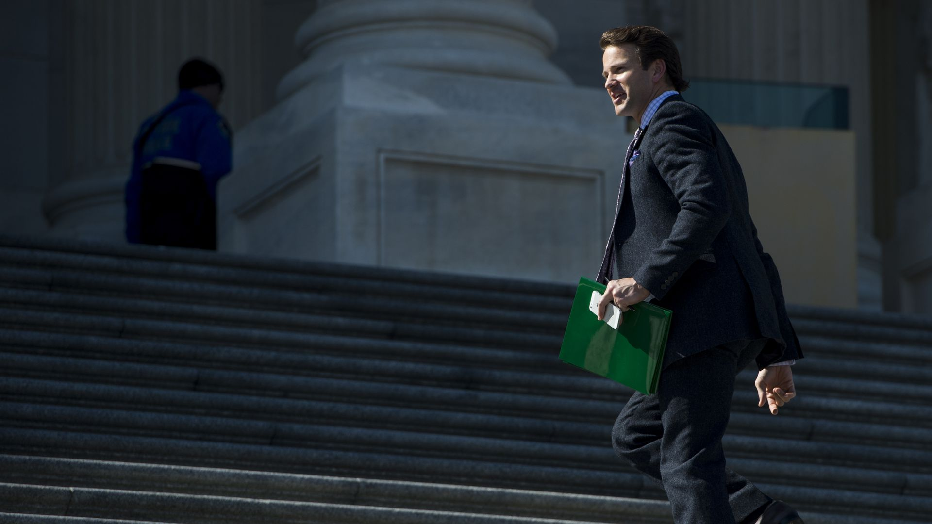 Former congressman Aaron Schock walks up the Capitol steps holding a green folder.