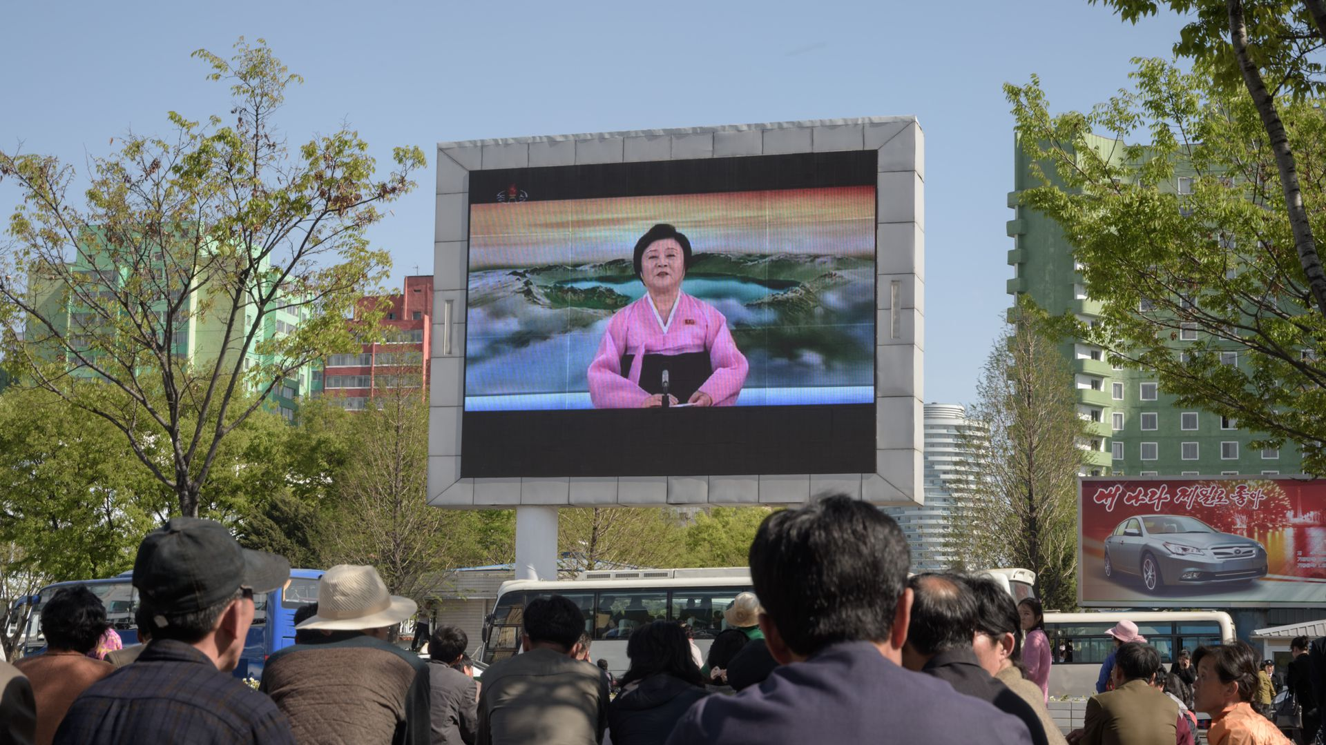 People watch a public television screen showing coverage of the 'Third Plenary Meeting' of the 7th central committee of the ruling Workers' Party, in Pyongyang