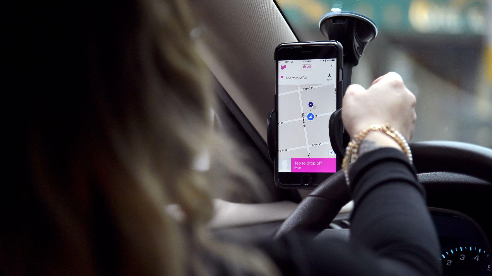 A Lyft driver navigates to her passenger.