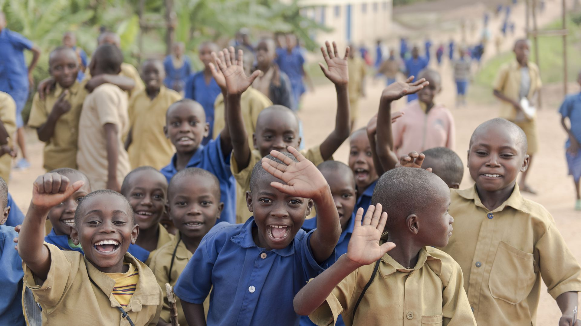 Primary school children wave after school in the Kyaumbu Sector of Rwanda.