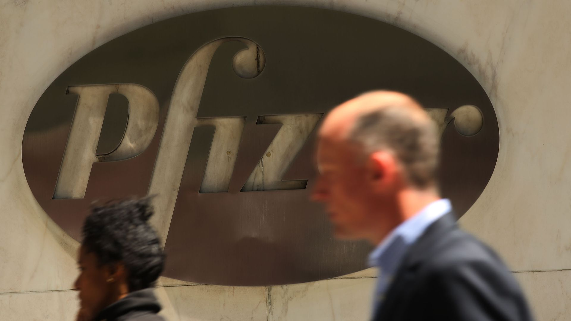 In this image, a man and a woman walk past a large metal logo for Pfizer
