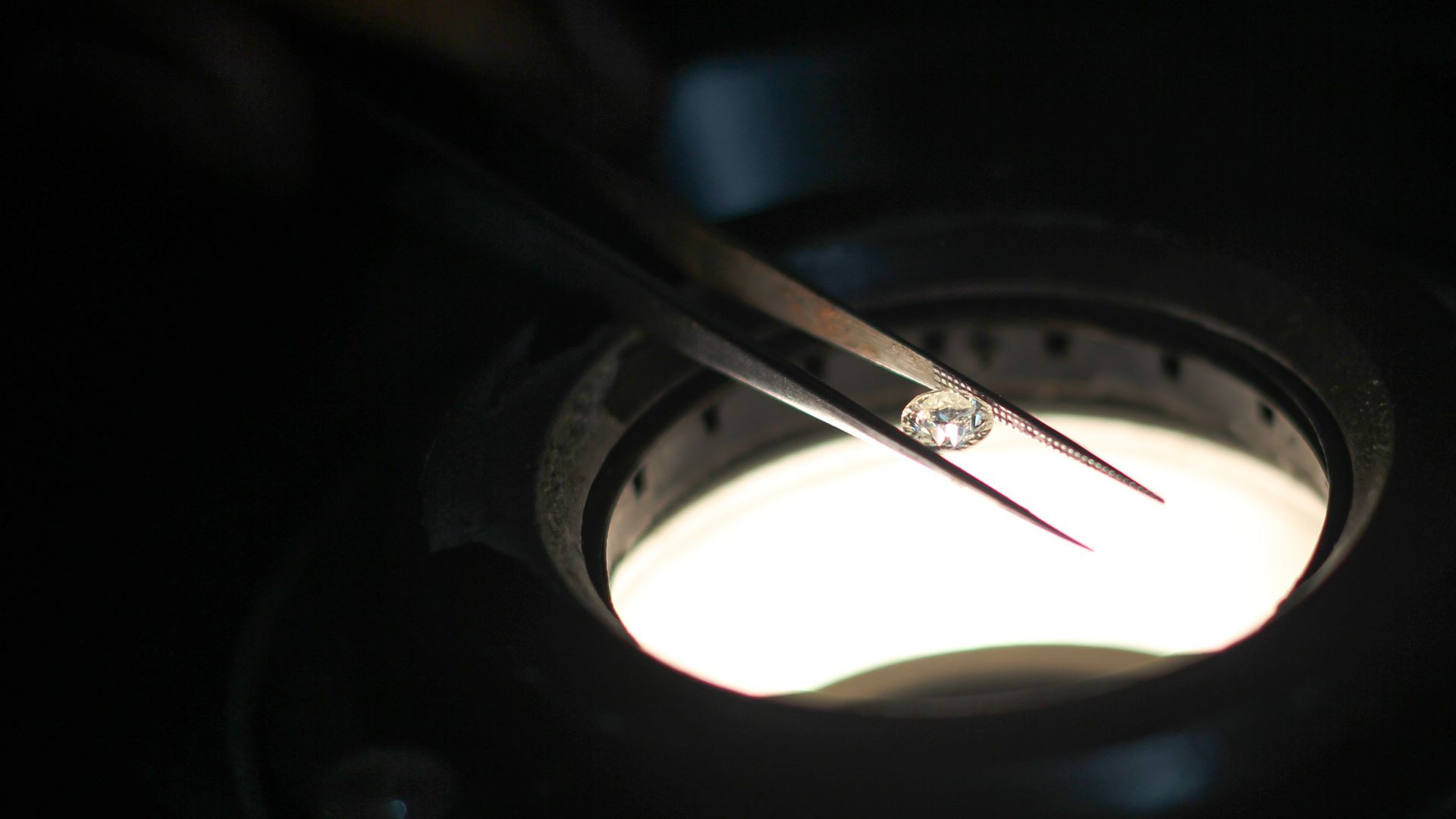 In this image, a small diamond is held between two long tweezers on top of a microscope.