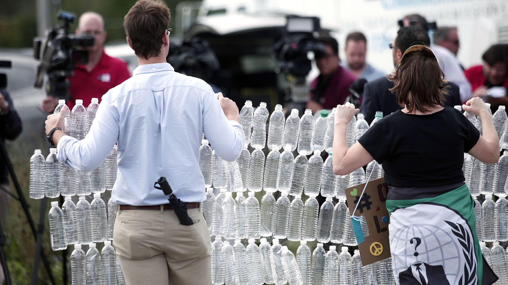 In this image, a man and a woman hold a connected chain of four rows of plastic water bottles while walking outside.