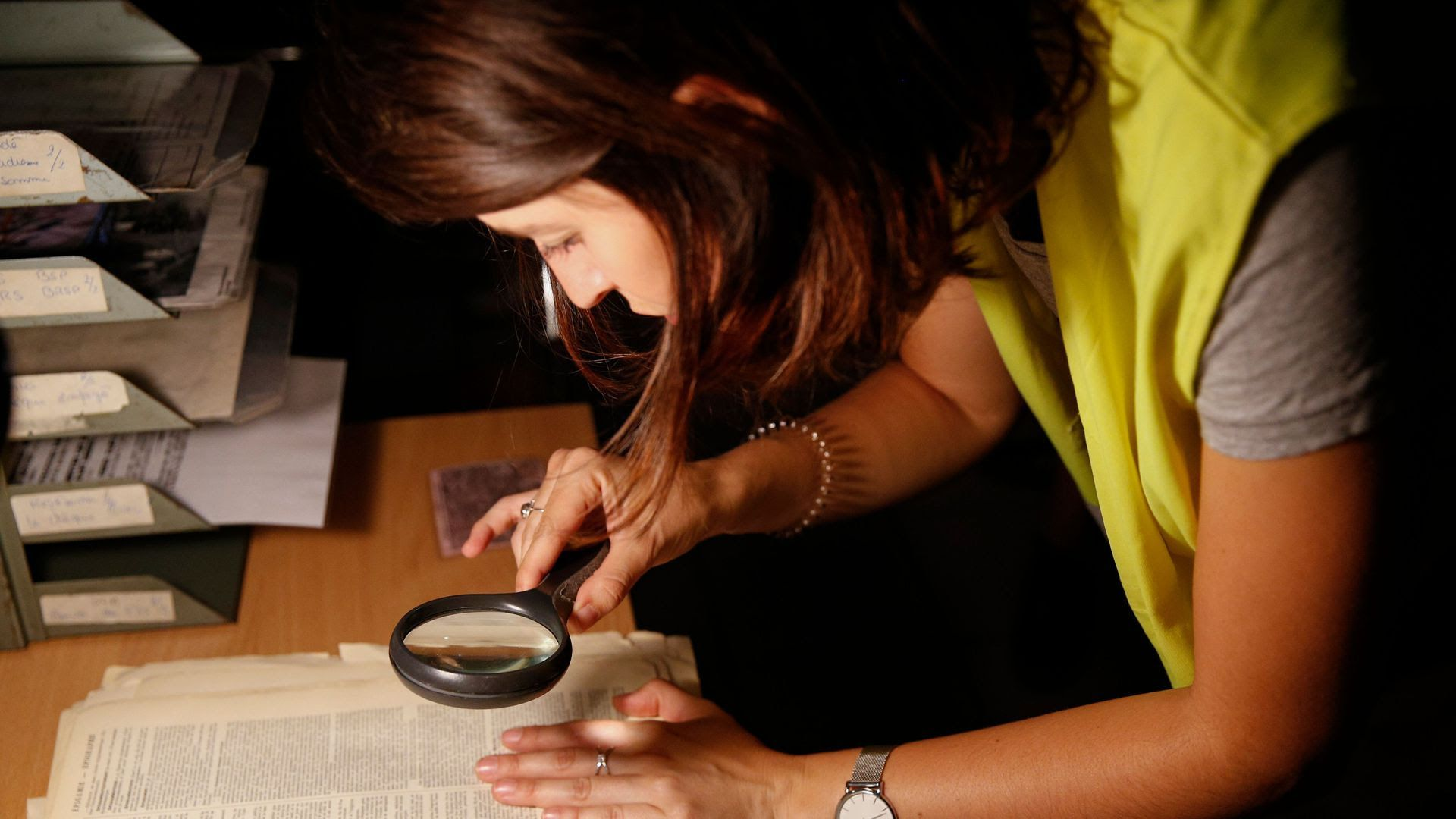 A woman searches for clues at an escape room.