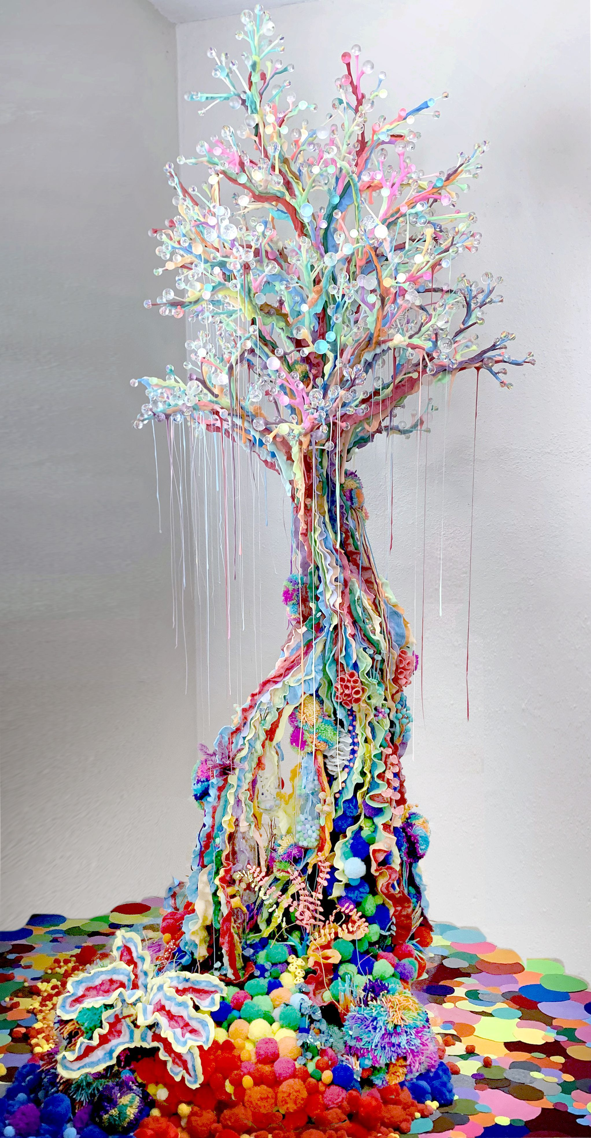 A colorful sculptural tree made out of pom-poms, resin, yarn, clay, and recycled materials.