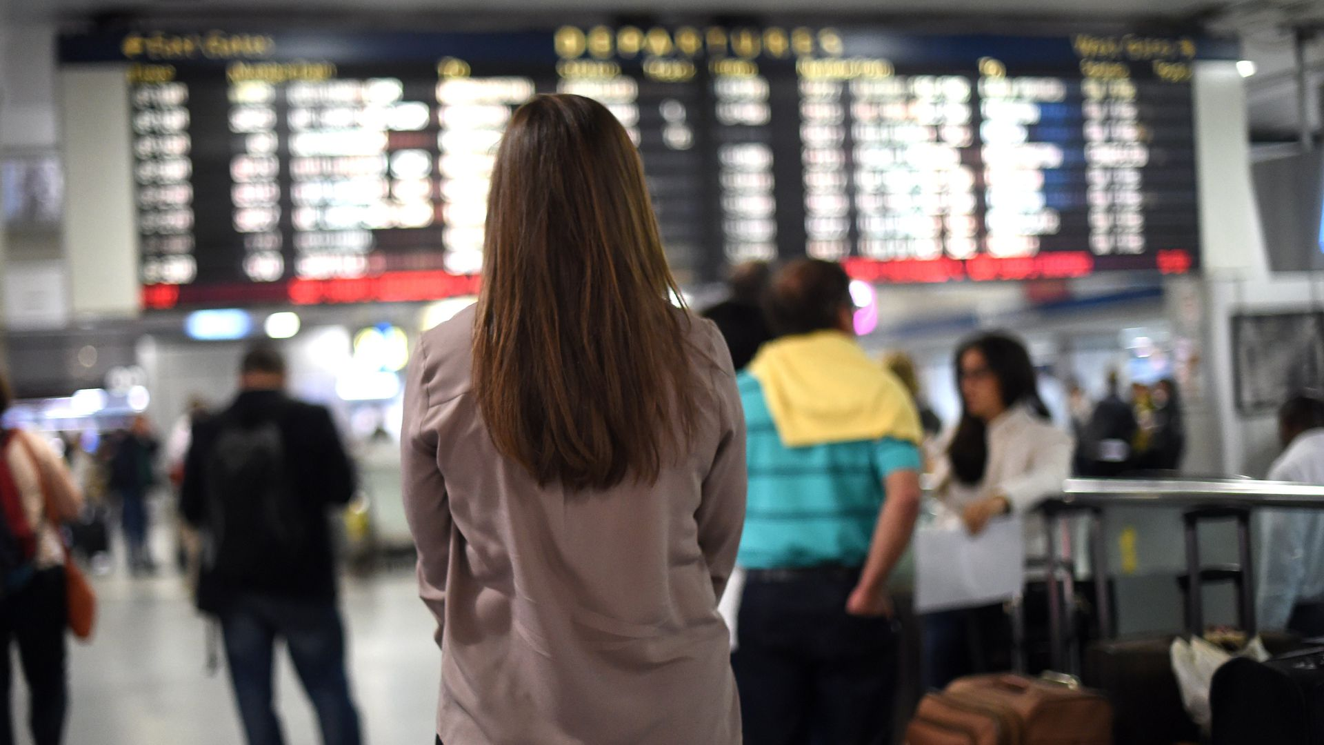 A woman in front of the departures board at Penn Station